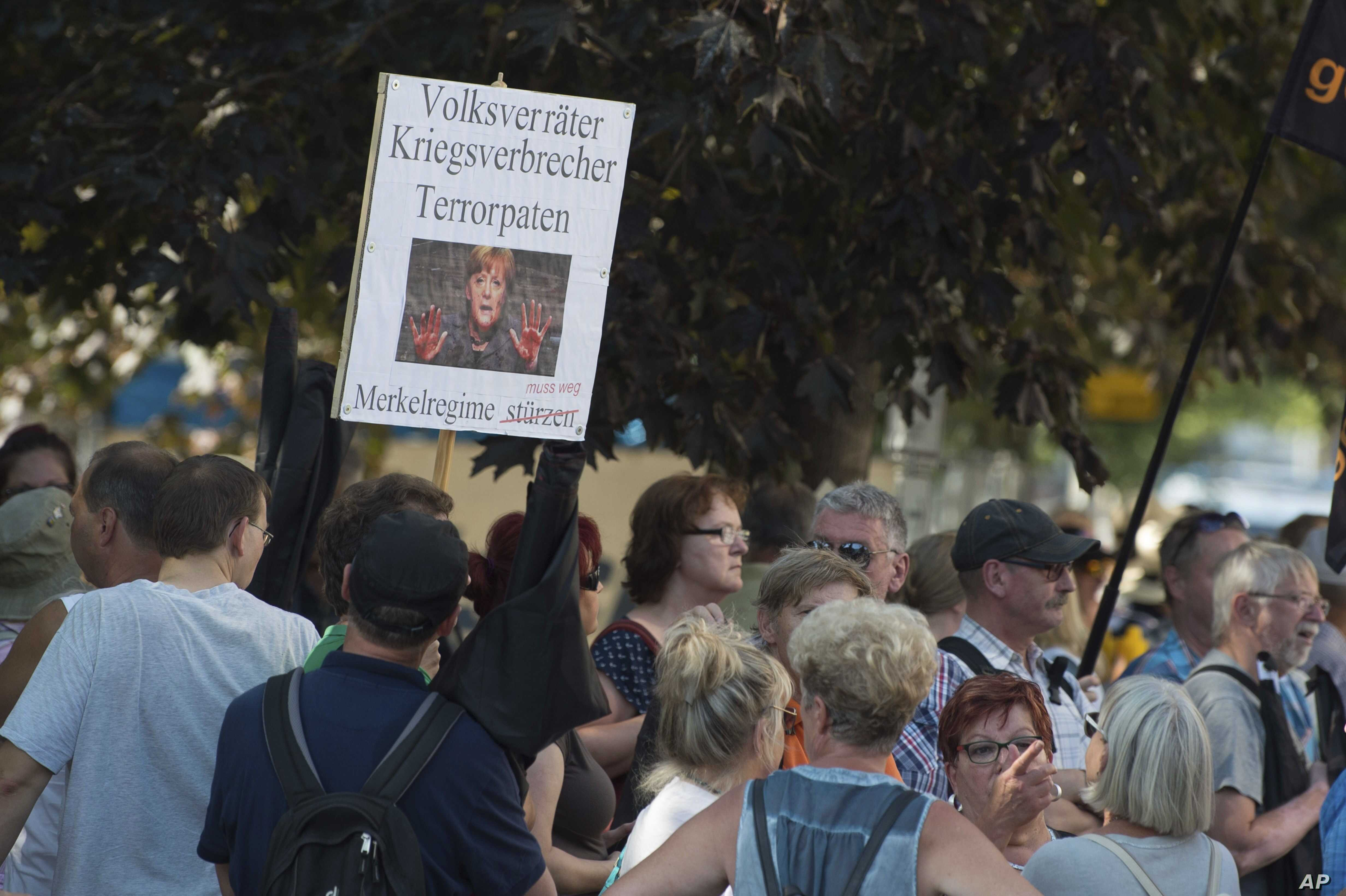 """Demonstrators hold a poster with a photo of Angela Merkel and the writing 'Traitor, war criminal, terror godparent - the Merkel regime must go"""" during Merkel's visit to Dresden, eastern Germany, Aug. 16, 2018."""