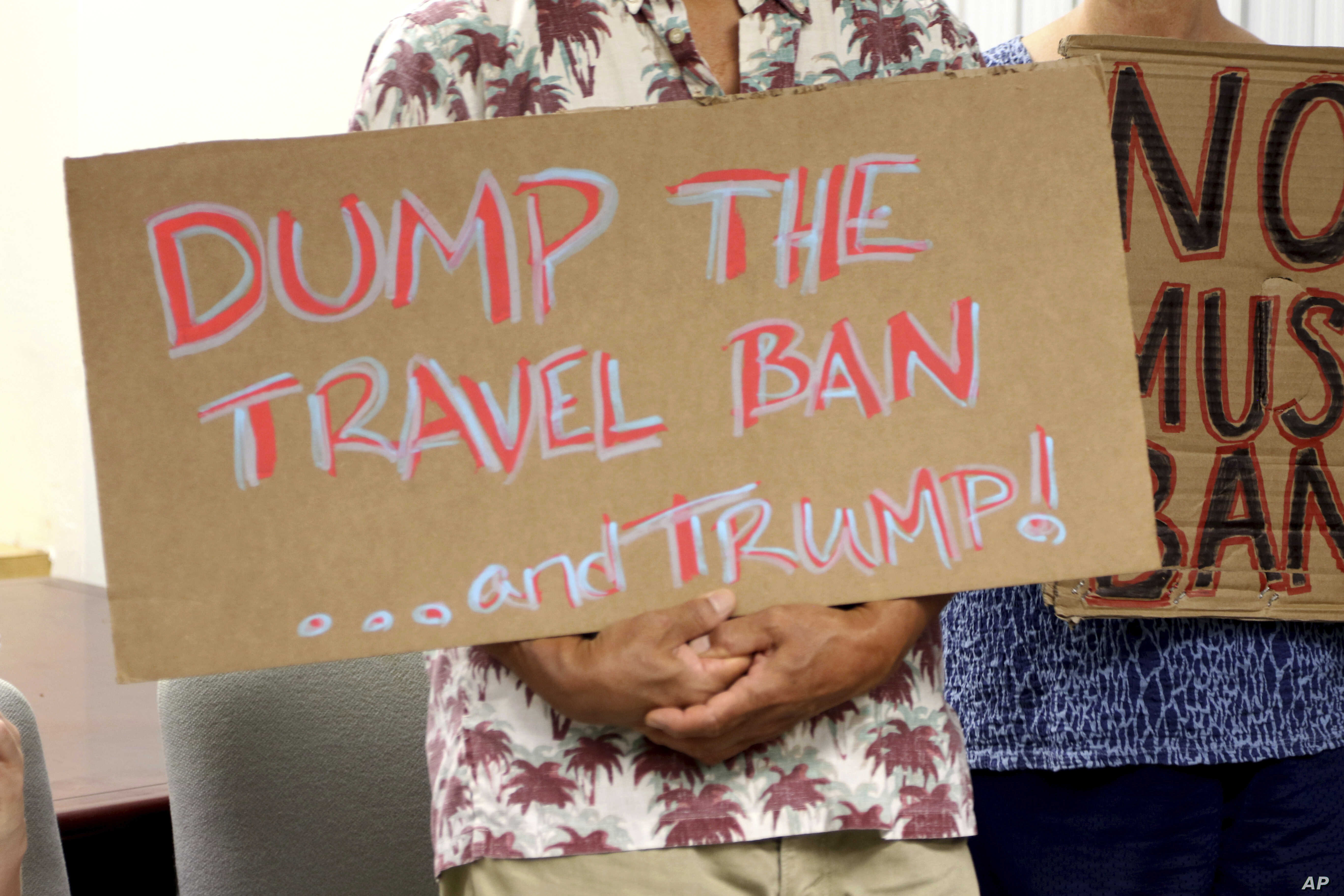 Critics of President Donald Trump's travel ban hold signs during a news conference with Hawaii Attorney General Douglas Chin, June 30, 2017 in Honolulu.