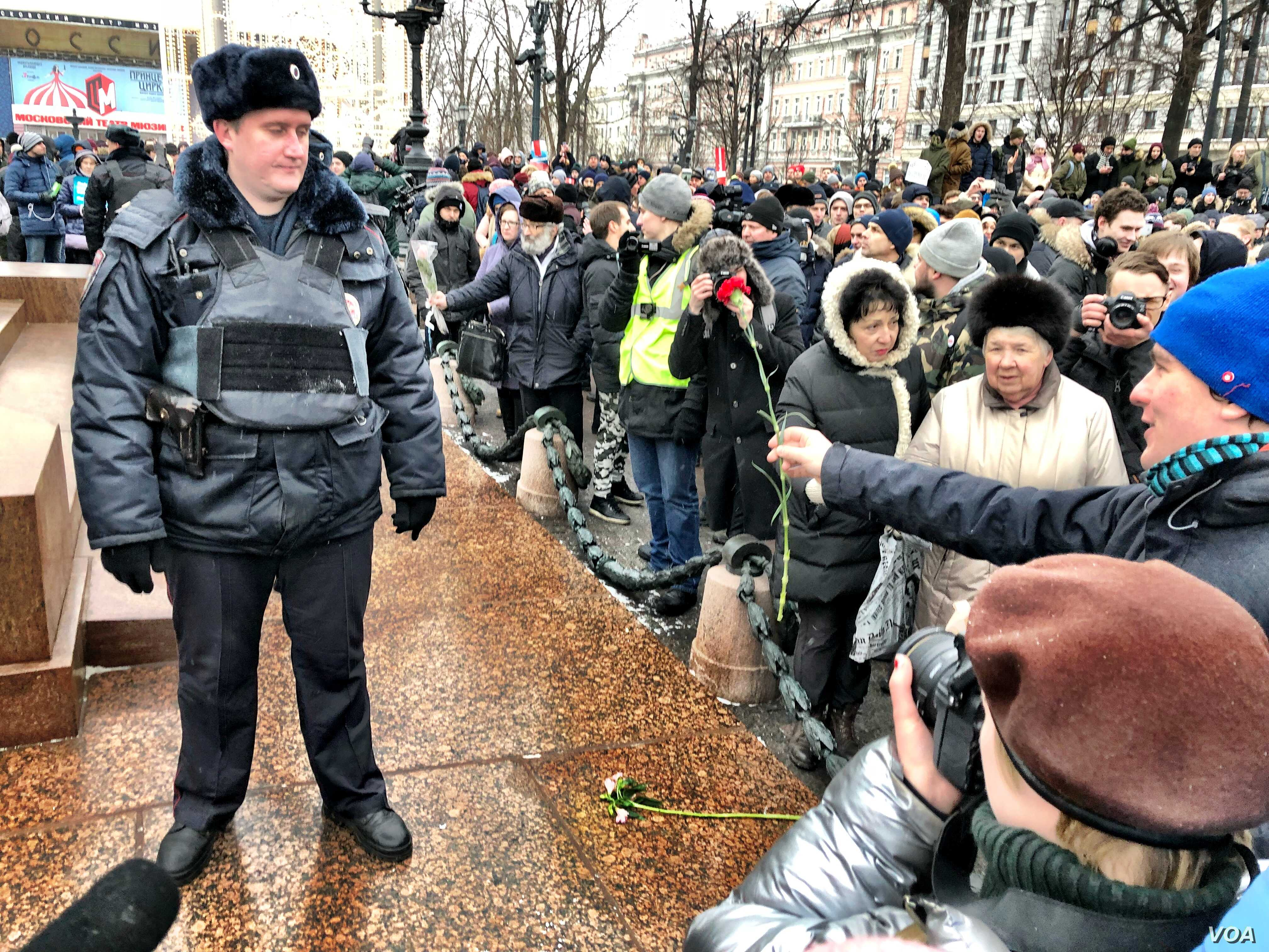 A protester in Moscow's Pushkin Square makes a peace offering to police.  Independent monitoring groups put arrests at 340 nationwide. (Photo: Charles Maynes for VOA)