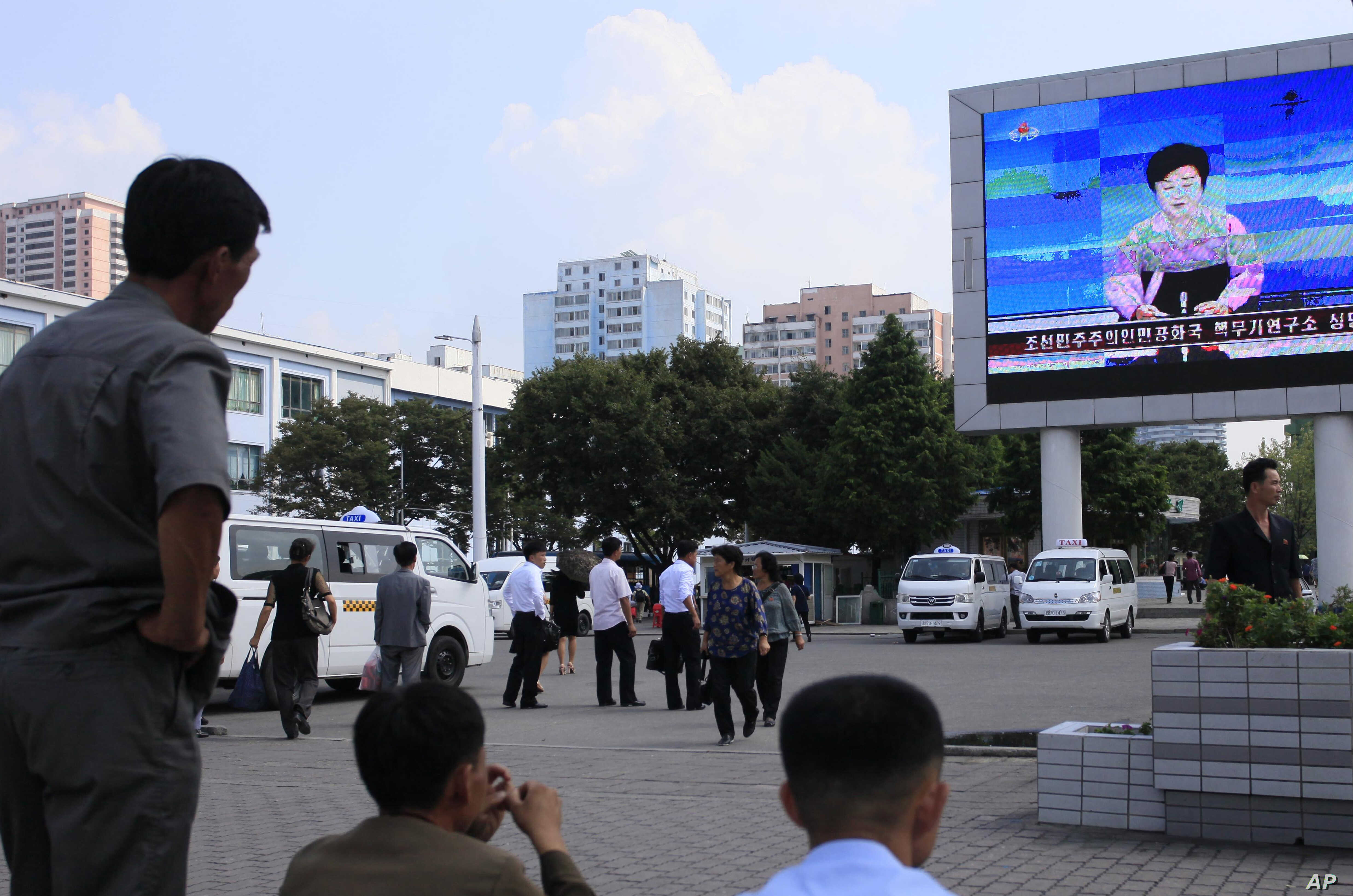 North Koreans watch a news report regarding a nuclear test on a large screen outside the Pyongyang Station in Pyongyang, North Korea, Friday, Sept. 9, 2016.