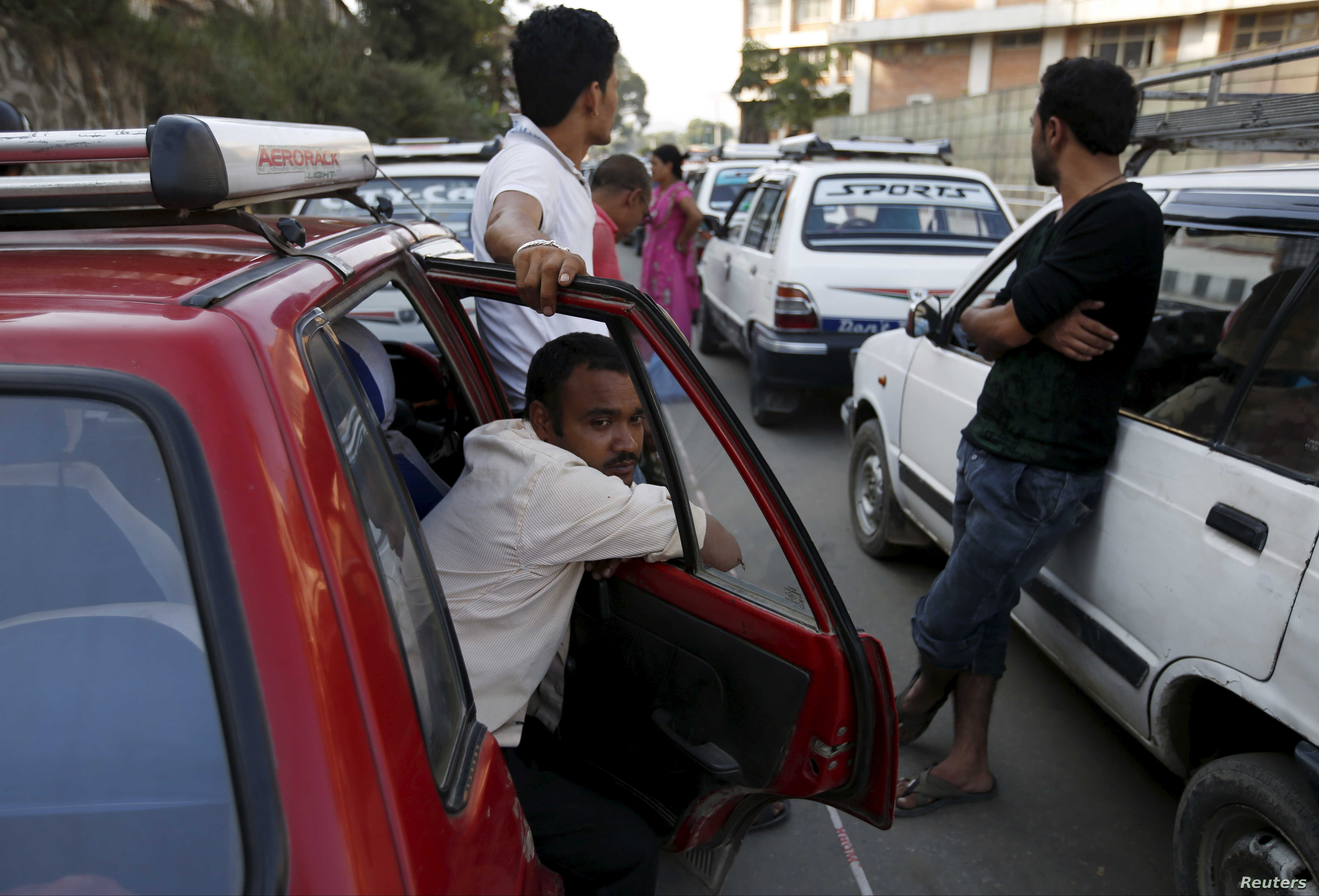 Drivers wait in a line to fill up their vehicles with fuel near a gasoline pump as the fuel crisis continues in Kathmandu, Nepal, Oct. 1, 2015.