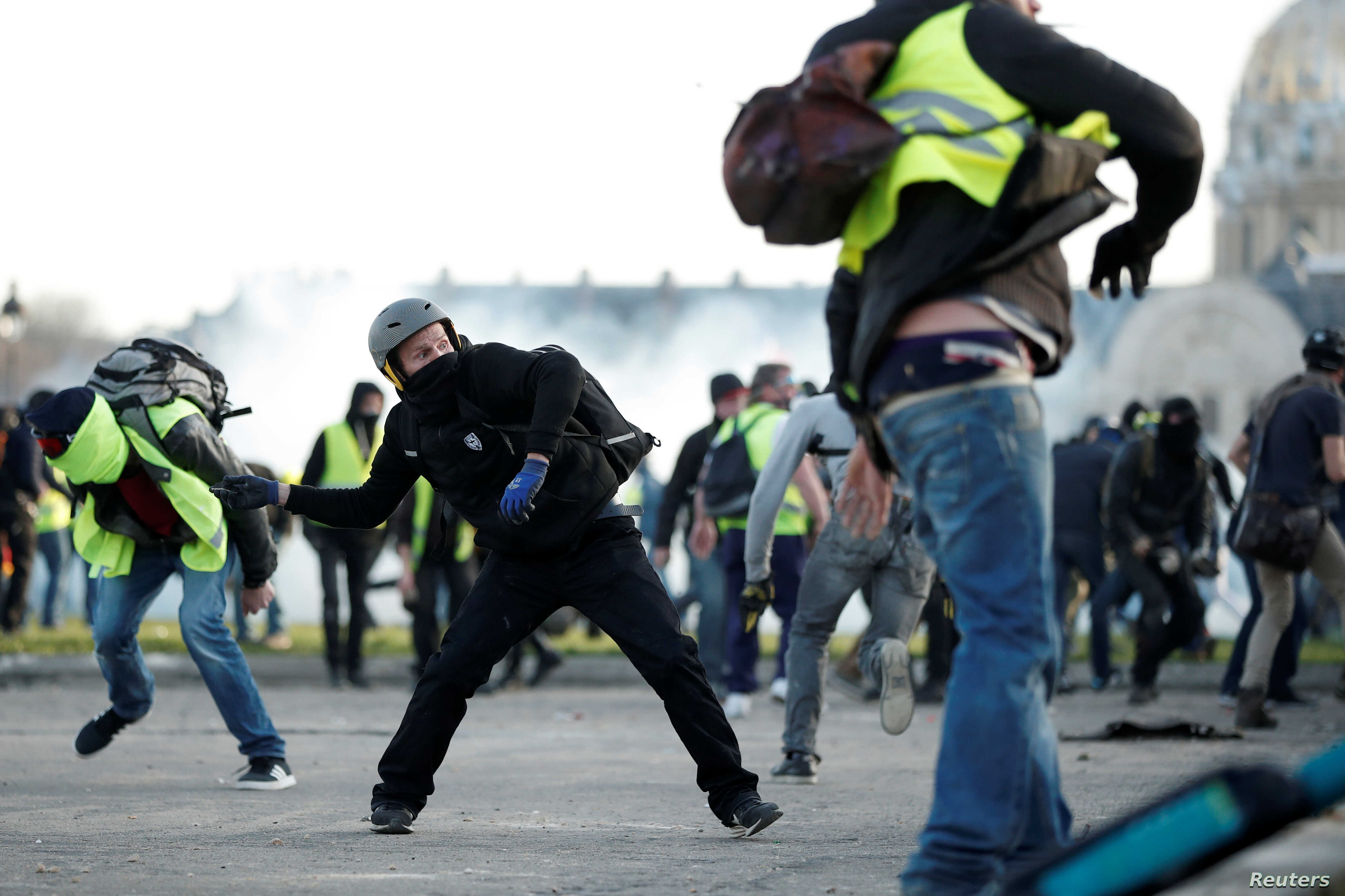 """Protesters wearing yellow vests clash with French riot police near the Invalides during a demonstration of the """"yellow vest"""" movement in Paris, Feb. 16, 2019."""