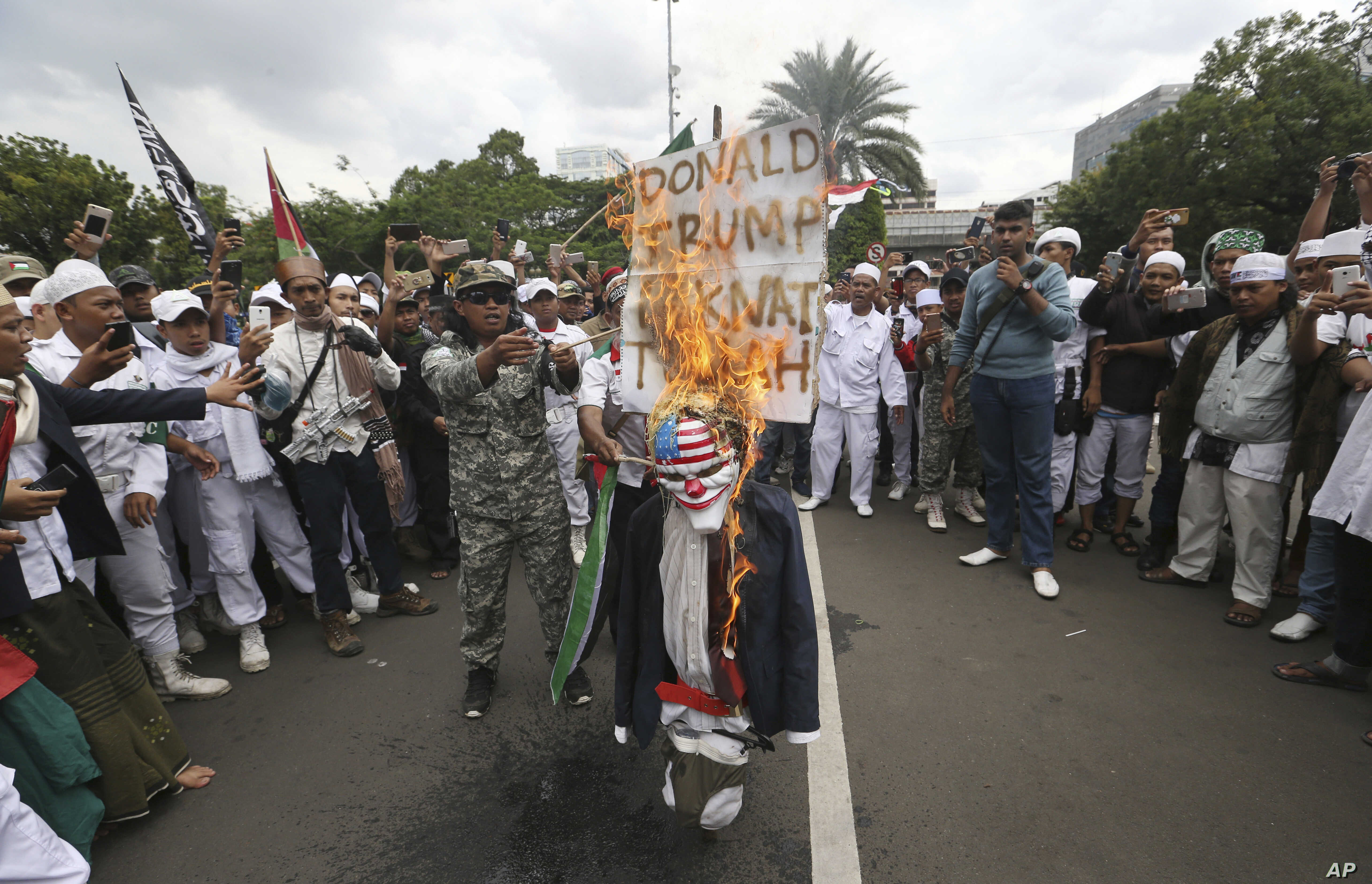 Protesters burn an effigy of U.S. President Donald Trump during a rally outside U.S. Embassy in Jakarta, Indonesia, Monday, Dec. 11, 2017. Hundreds of people staged the protest in the Indonesian capital of Jakarta to denounce Trump's decision to reco...