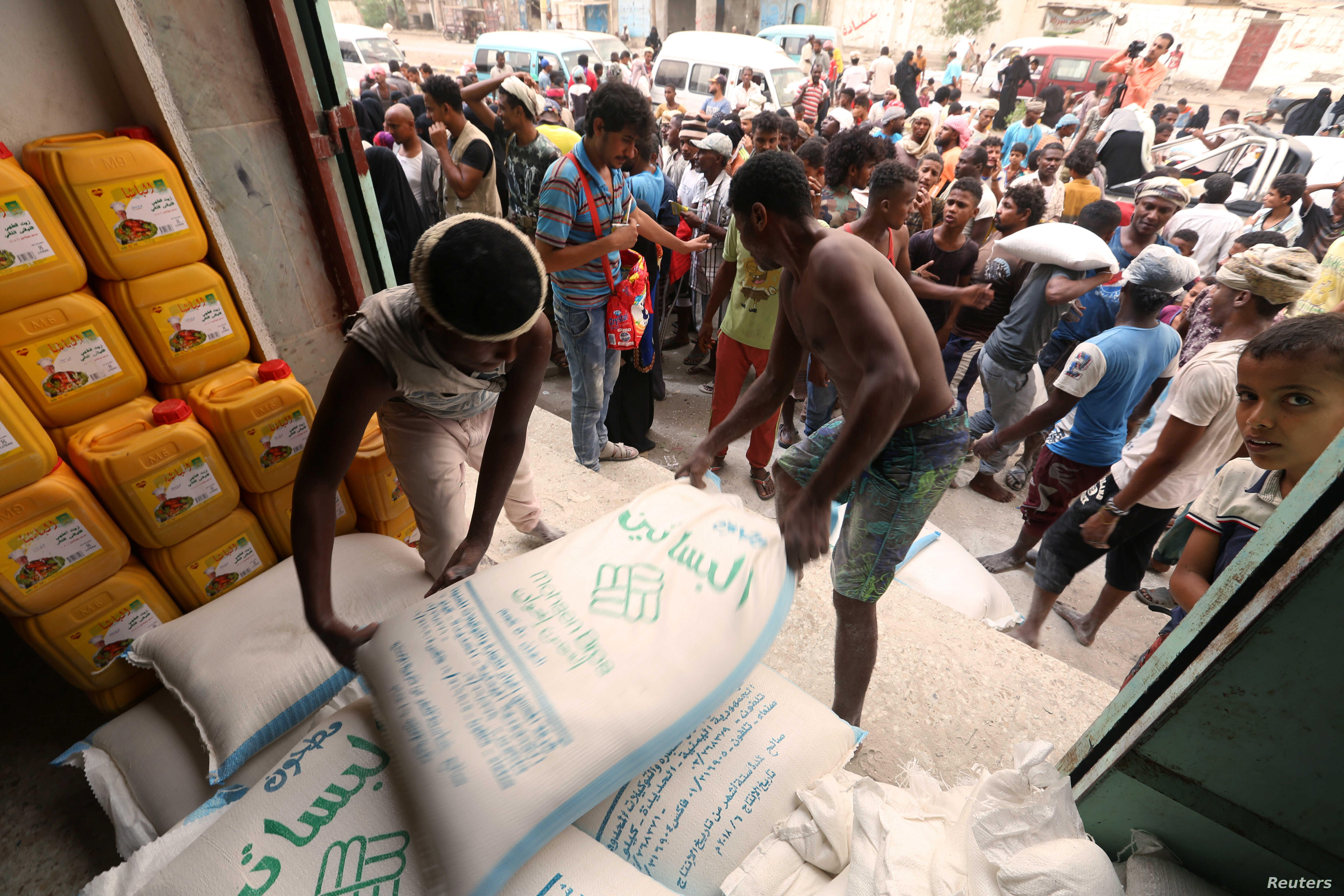 Workers unload sacks of wheat flour as people gather outside an aid distribution center in the Red Sea port city of Hodeidah, Yemen, June 14, 2018.