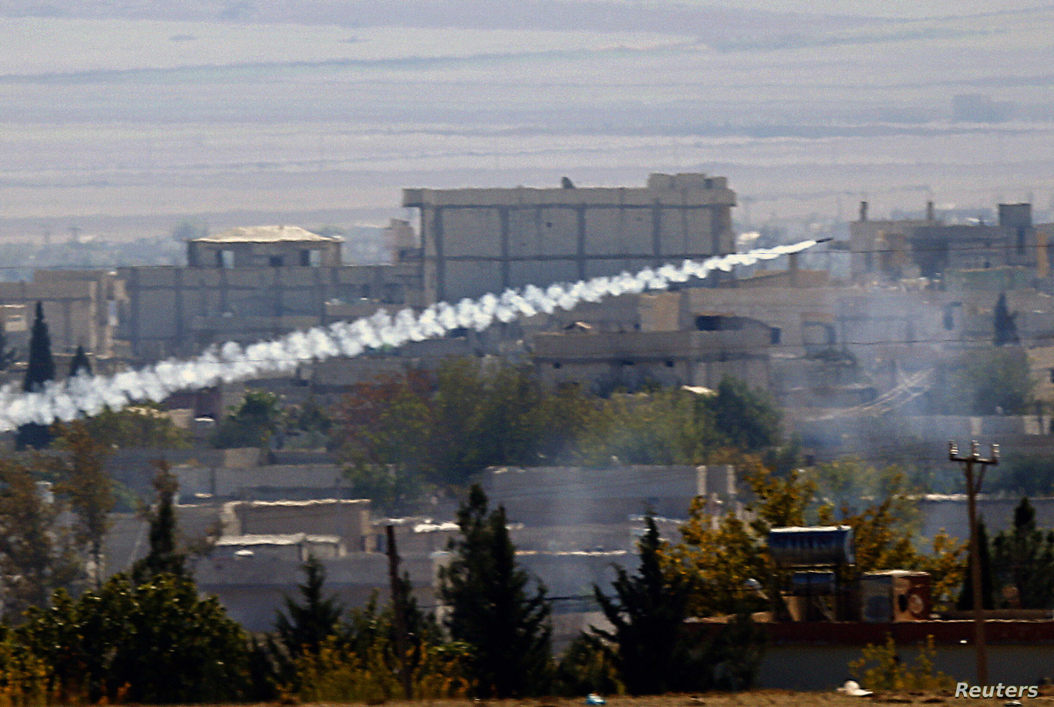 FILE - A rocket believed to have been launched by Islamic State forces flies from the east to the west side of the Syrian town of Kobani during fighting, Nov. 6, 2014 Picture taken from the Turkish side of the Turkey-Syria border.