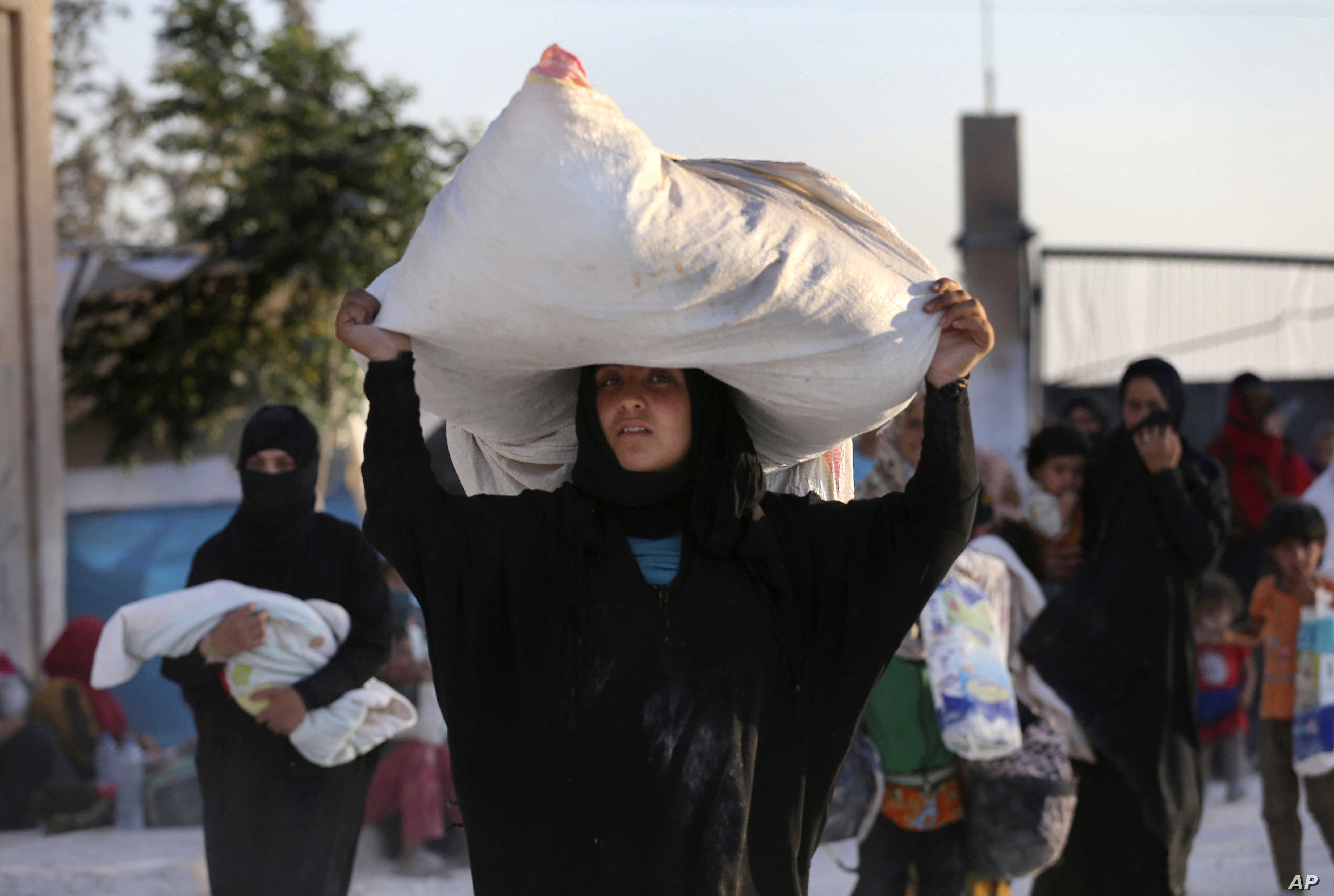 A Syrian woman who fled with her family the battle between U.S.-backed Syrian Democratic Forces (SDF) and the Islamic State militants from Raqqa city, carries her belongings upon her arrival at a refugee camp, in Ain Issa, July 24, 2017.