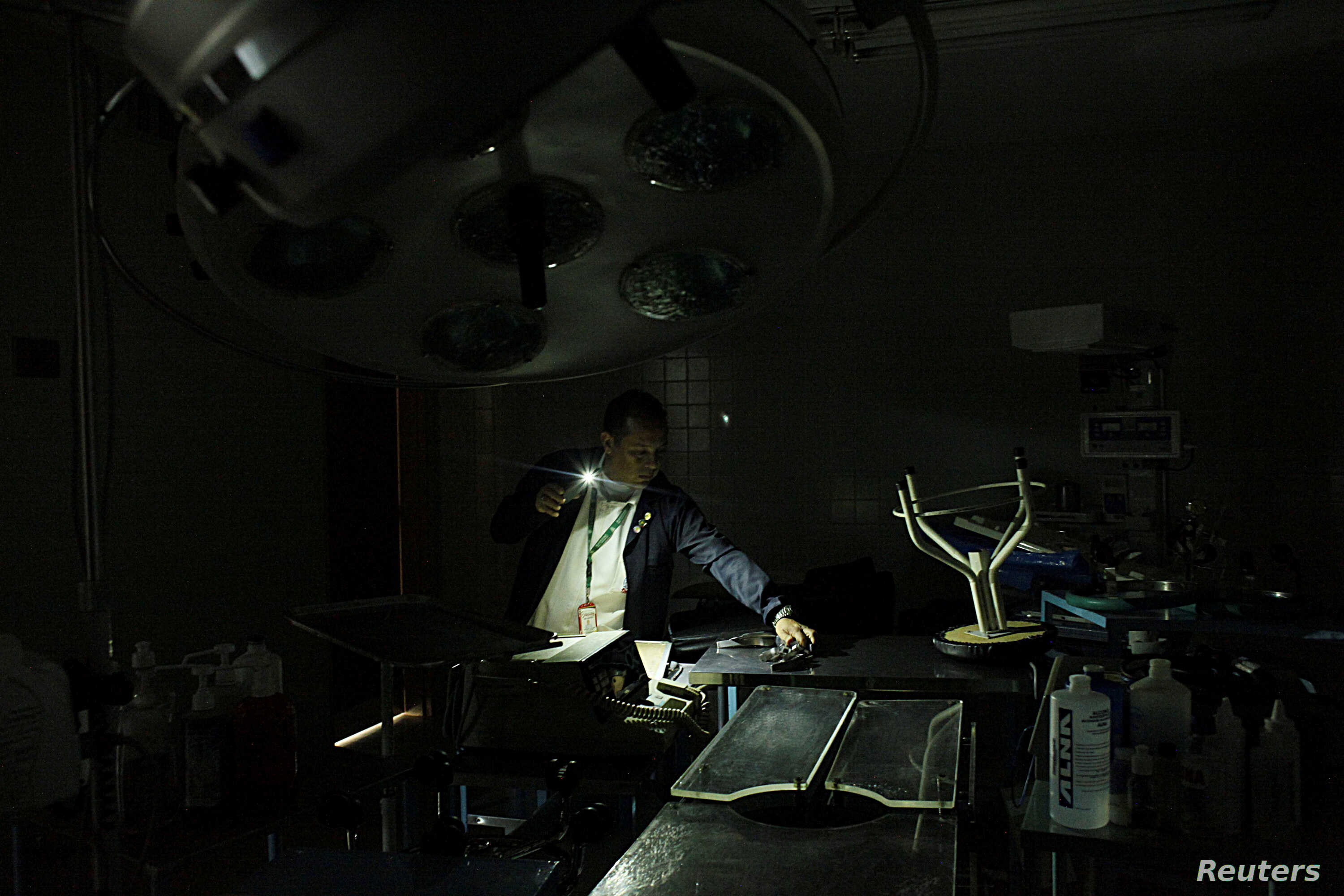 A nurse uses light from a phone while he looks for material in an out-of-use operating room of the Padre Justo hospital, during a blackout in Rubio, Venezuela, March 14, 2018.