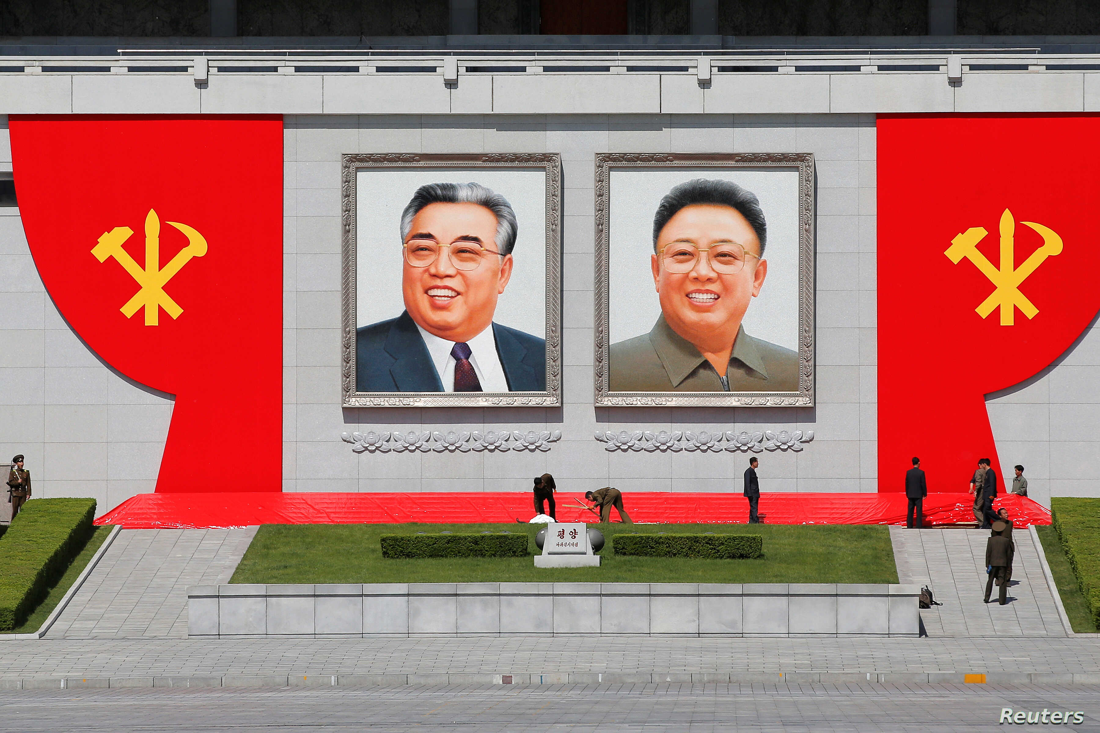 People work around pictures of former North Korean leaders Kim Il Sung, left, and Kim Jong Il at the main Kim Il Sung square in central Pyongyang, North Korea, May 7, 2016.