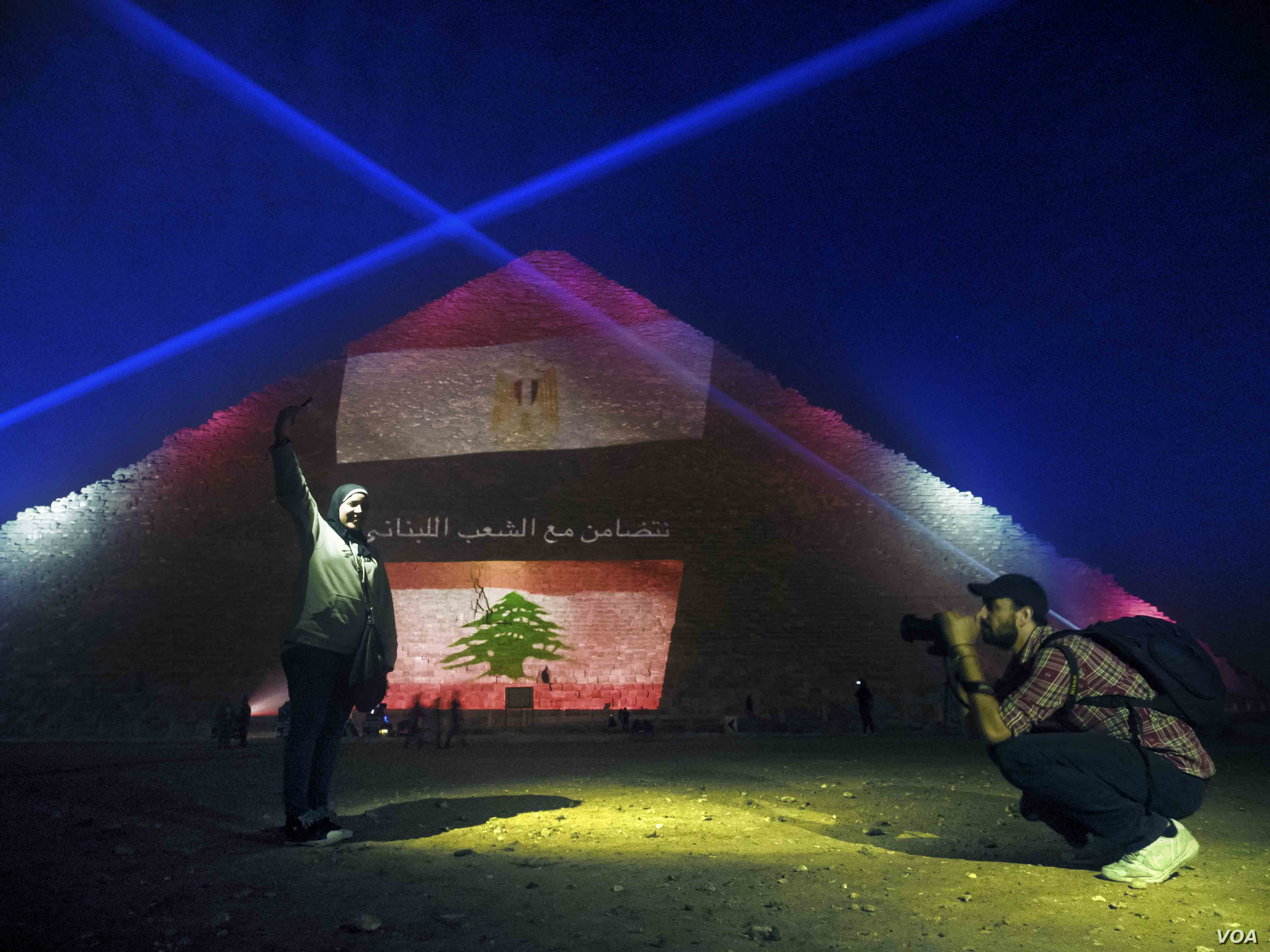 The usual light show at the Giza pyramid complex in Egypt was suspended on Sunday, replaced by lights depicting Lebanese, French and Russian flags and messages of solidarity, Nov. 15, 2015. (VOA/Hamada Elrasam/VOA)