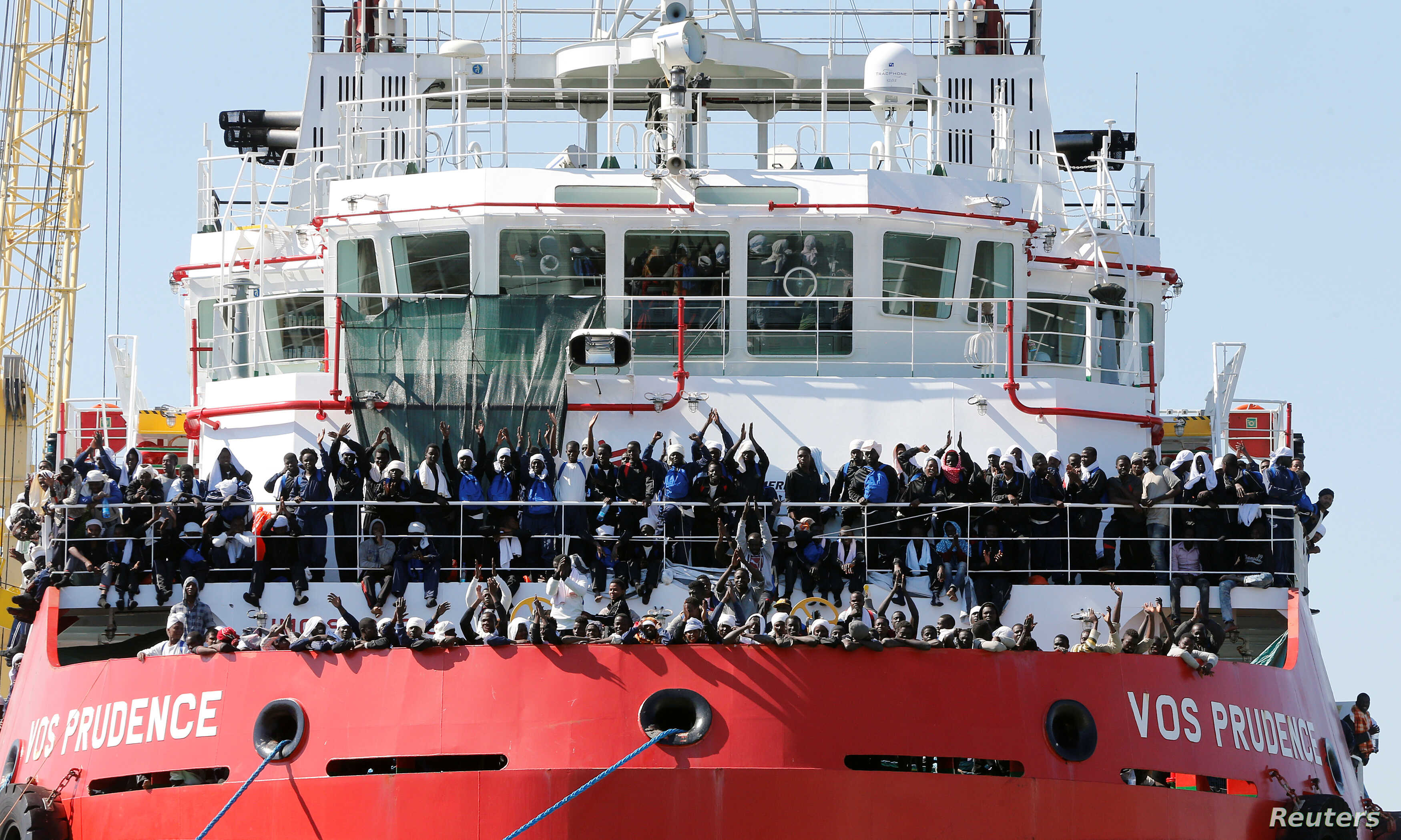 "FILE - Migrants wait to disembark from ""Vos Prudence"" offshore tug supply ship as they arrive at the harbor in Naples, Italy, May 28, 2017."