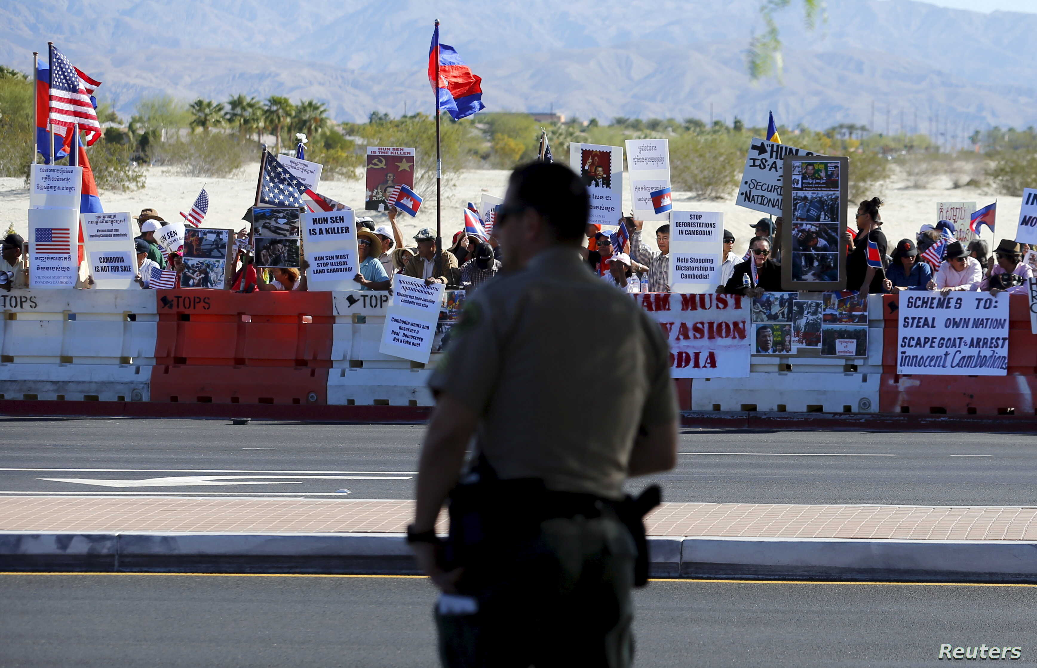 A police officer looks on as protesters line one side of a roadway leading to Sunnylands where U.S. President Obama prepares to host leaders from Southeast Asia at the ASEAN Summit in Rancho Mirage, California, Feb. 15, 2016.