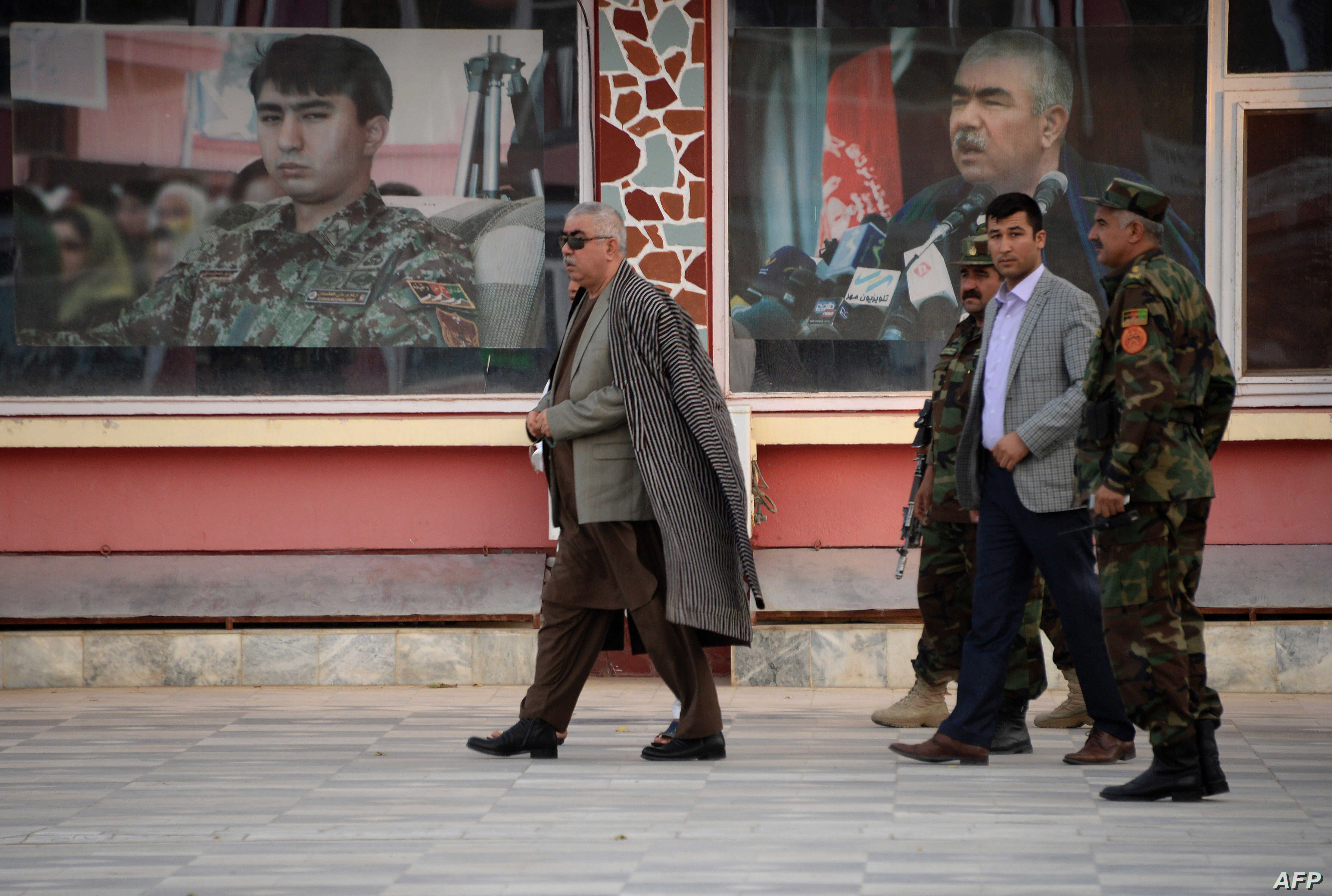 Afghan first vice-president Abdul Rashid Dostum (L) walks at his headquarters in Sheberghan, capital of northern Jowzjan province, July 28, 201.