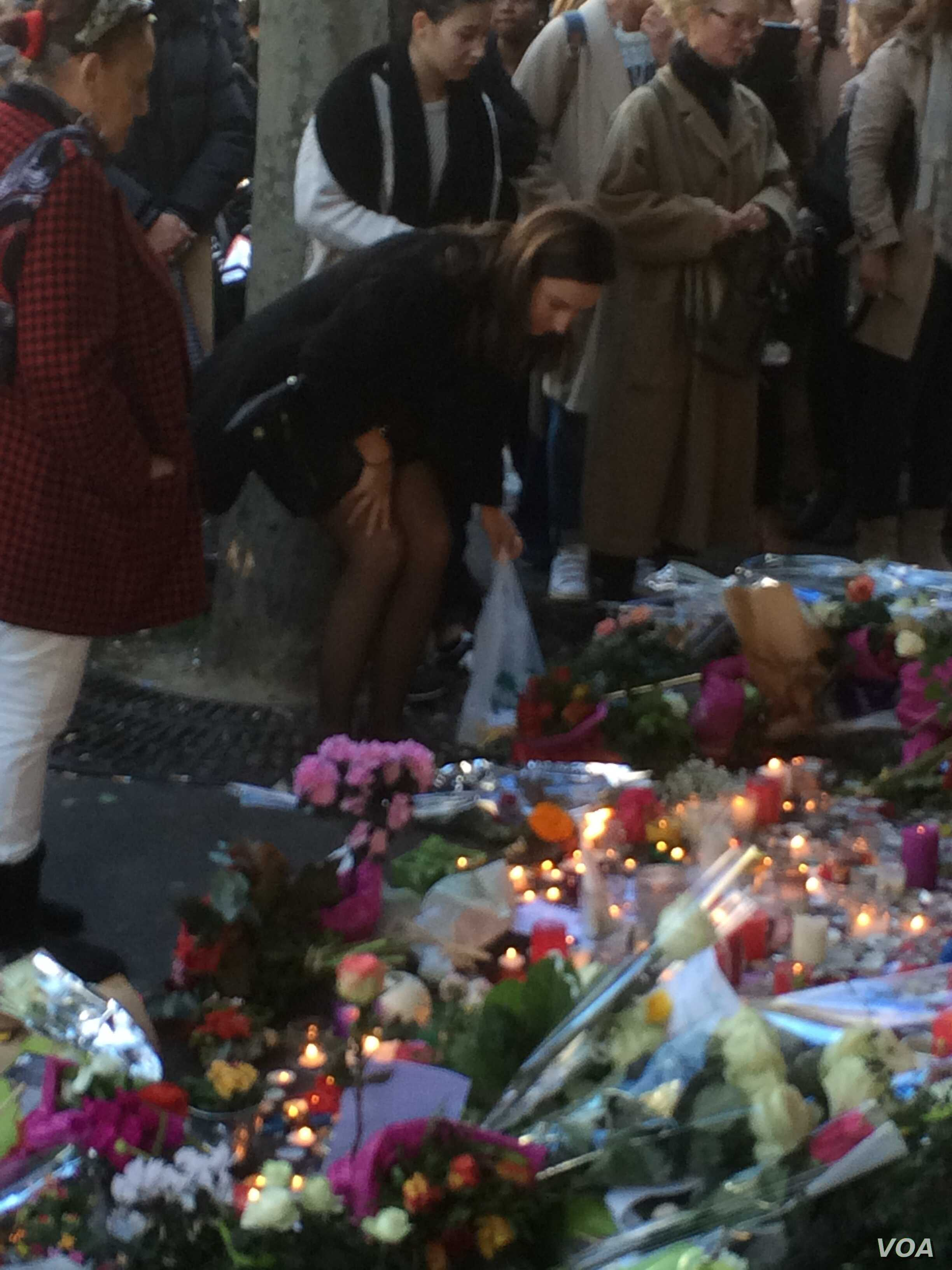 Visitors lay flowers at a memorial near La Belle Equipe bar in the rue de Charonne, where one of Friday's attacks occurred, in Paris, Nov. 15, 2015.