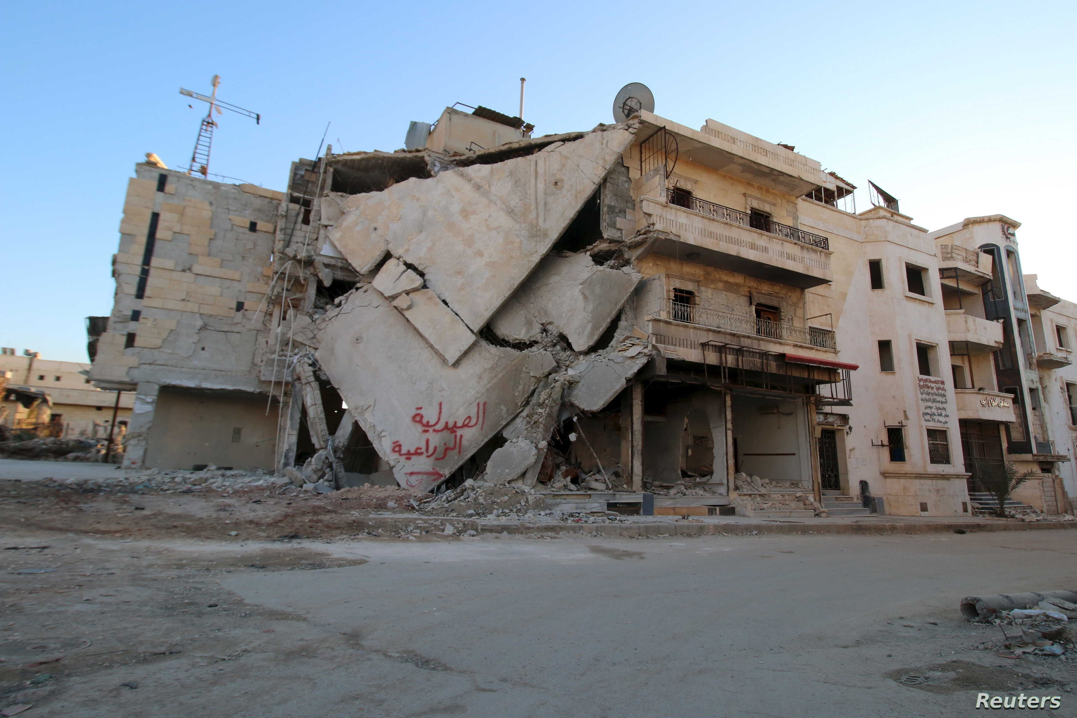 "A damaged building is seen in Hraytan city, about 10 kilometers away from the towns of Nubul and Zahraa, Northern Aleppo countryside, Syria, Feb. 3, 2016. The text on the building reads in Arabic: ""Agricultural pharmacy."""