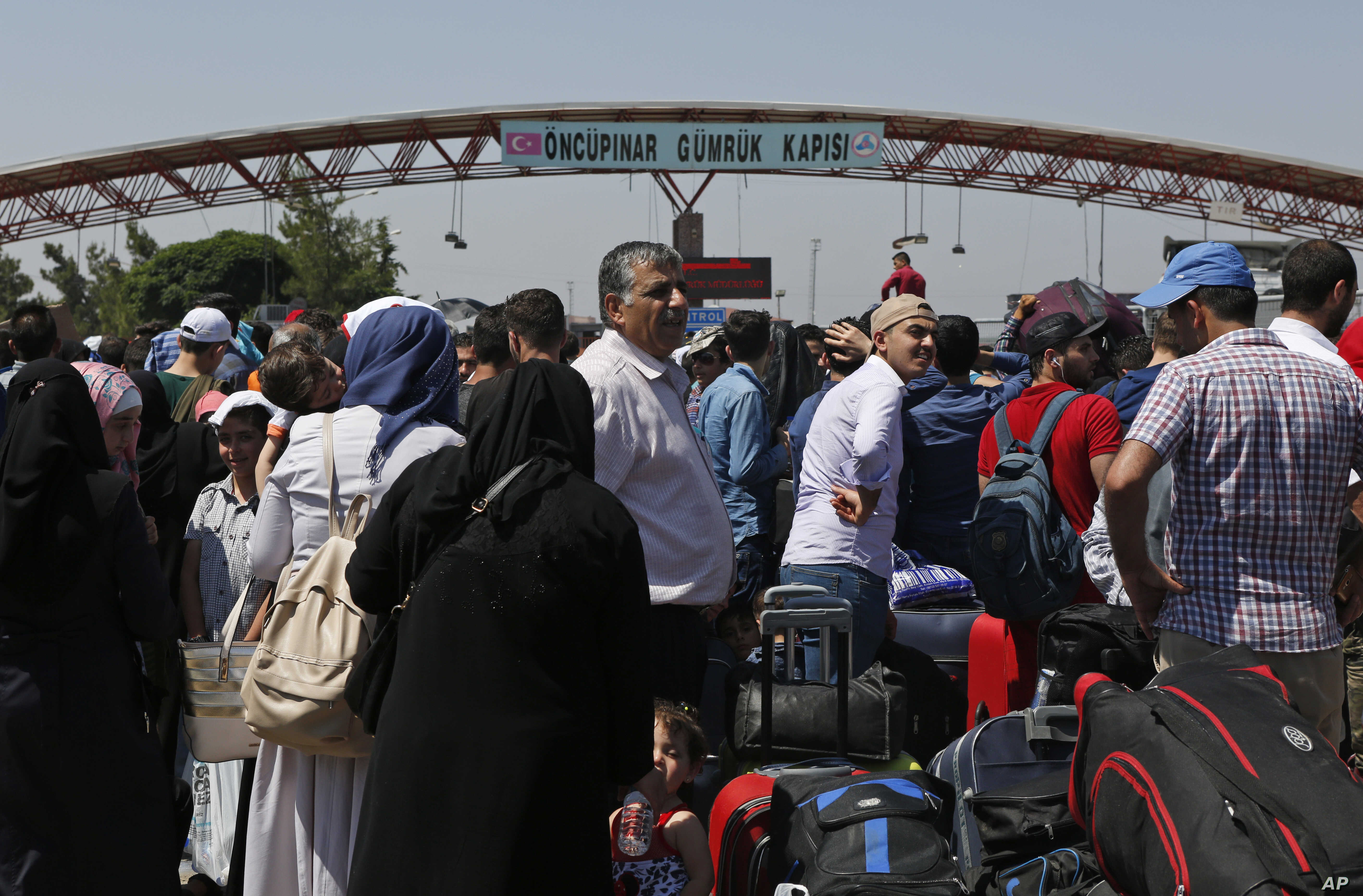 In this June 13, 2017 photo, Syrians living in Turkey wait to cross into Syria at the Oncupinar border crossing, near the town of Kilis, Turkey.