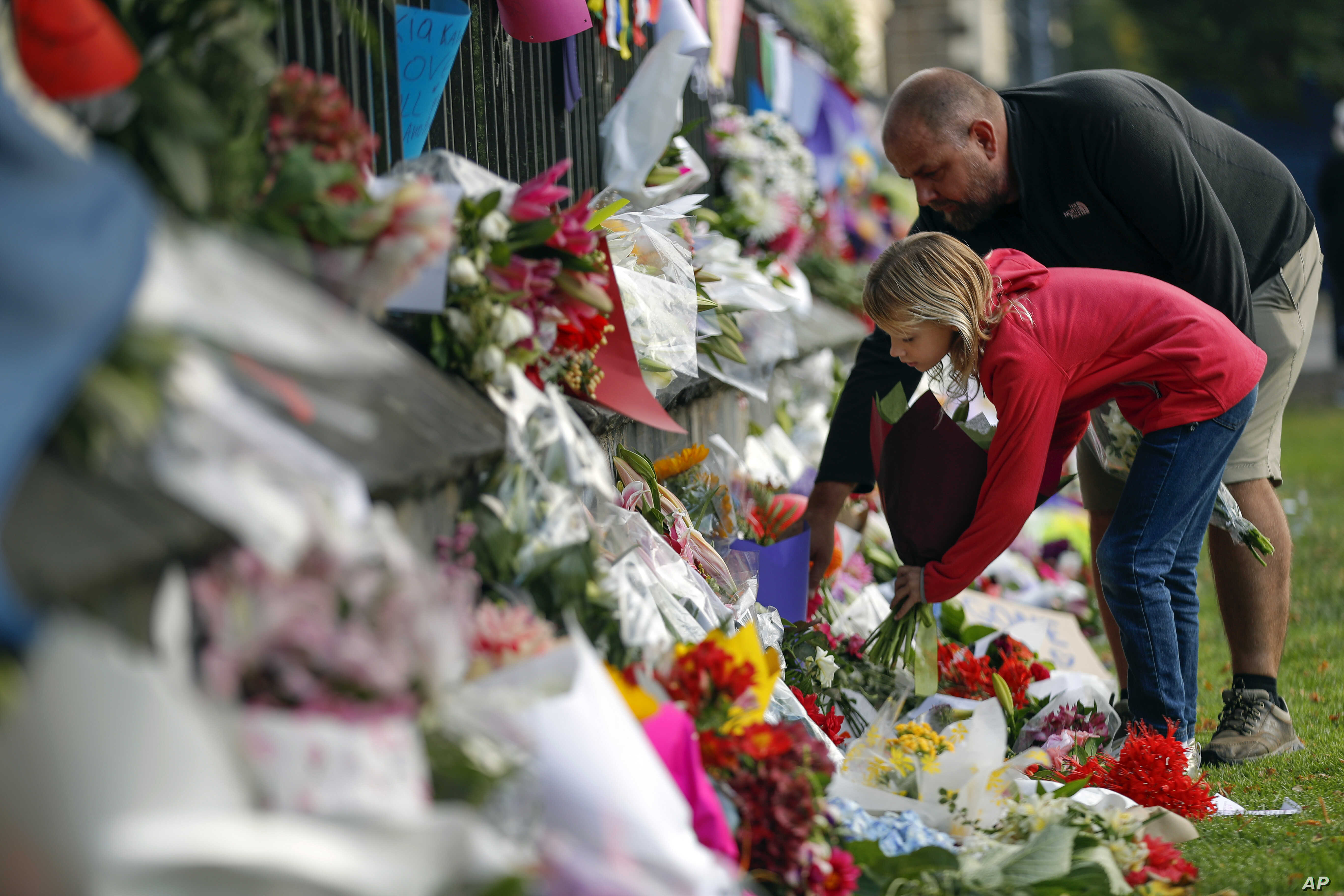 Mourners lay flowers on a wall at the Botanical Gardens in Christchurch, New Zealand, March 16, 2019. New Zealand's stricken residents reached out to Muslims in their neighborhoods and around the country Saturday, in a fierce determination to show ki