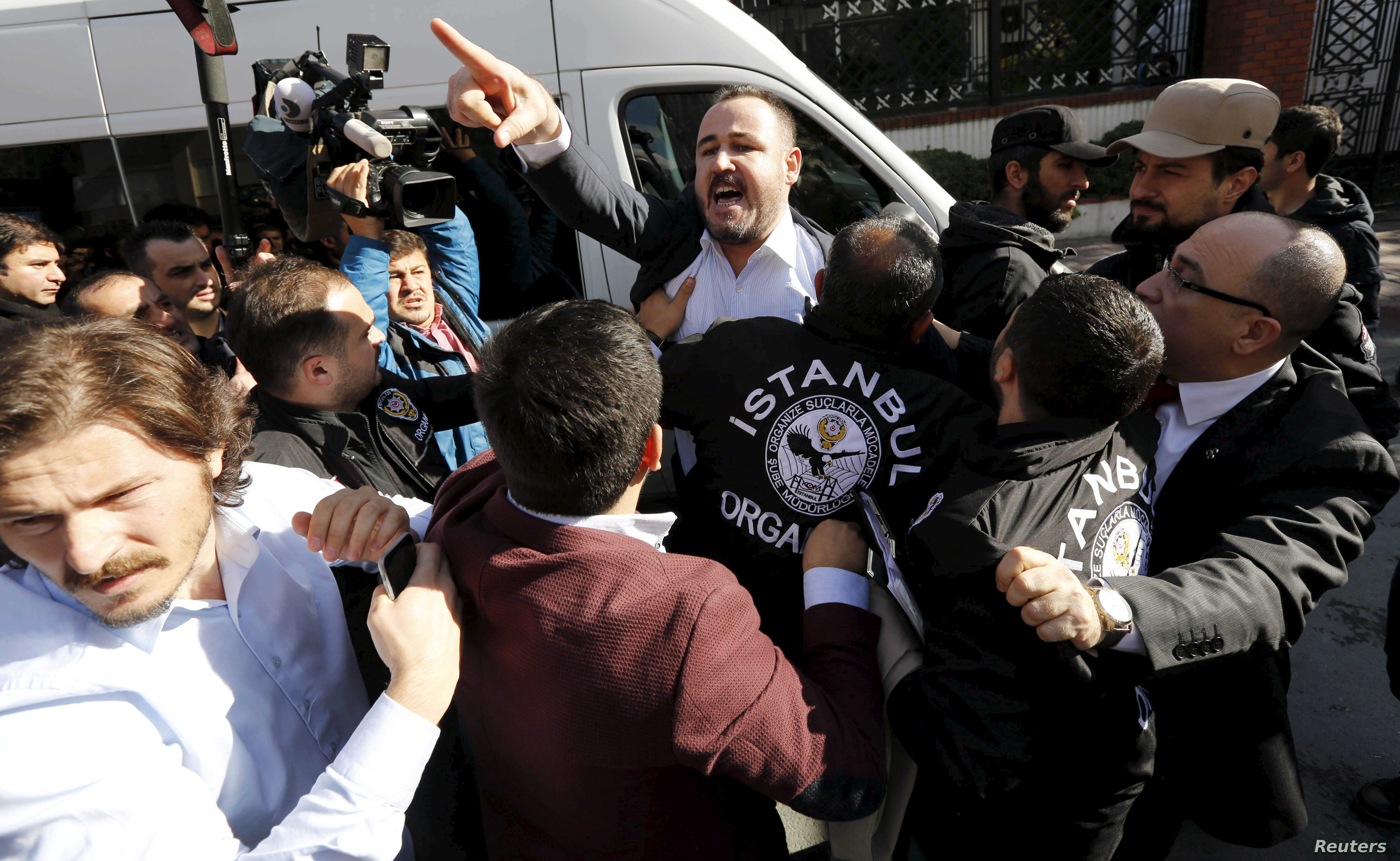 Plainclothes police officers scuffle with a protester outside the Kanalturk and Bugun TV building in Istanbul, Turkey, Oct. 28, 2015.