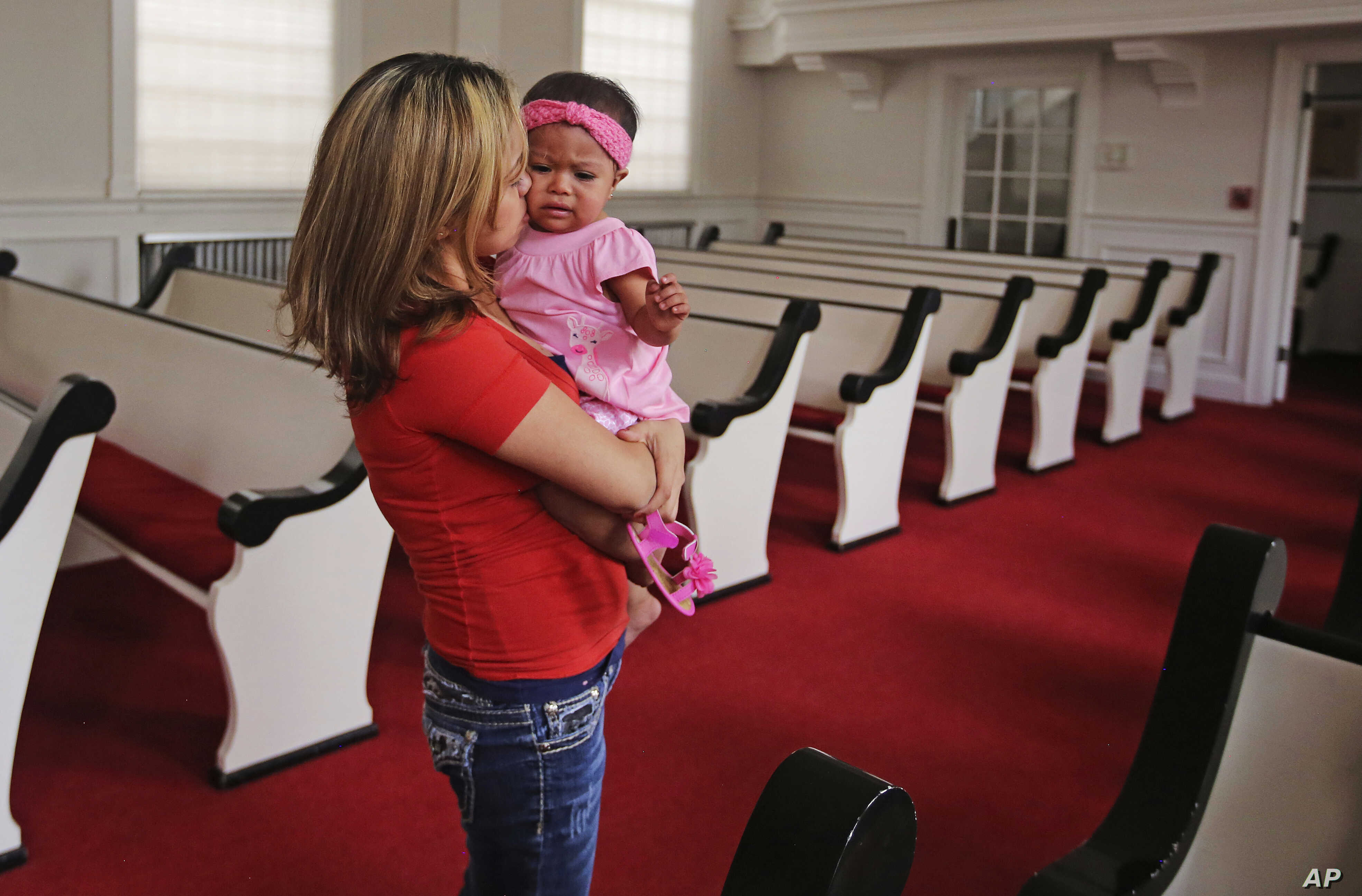 Vicky Chavez comforts her daughter Issabella in the First Unitarian Church, in Salt Lake City, Utah, May 31, 2018. Chavez says seeing fellow Central Americans separated from their children at the U.S.-Mexico border makes her intent on trying to fight...