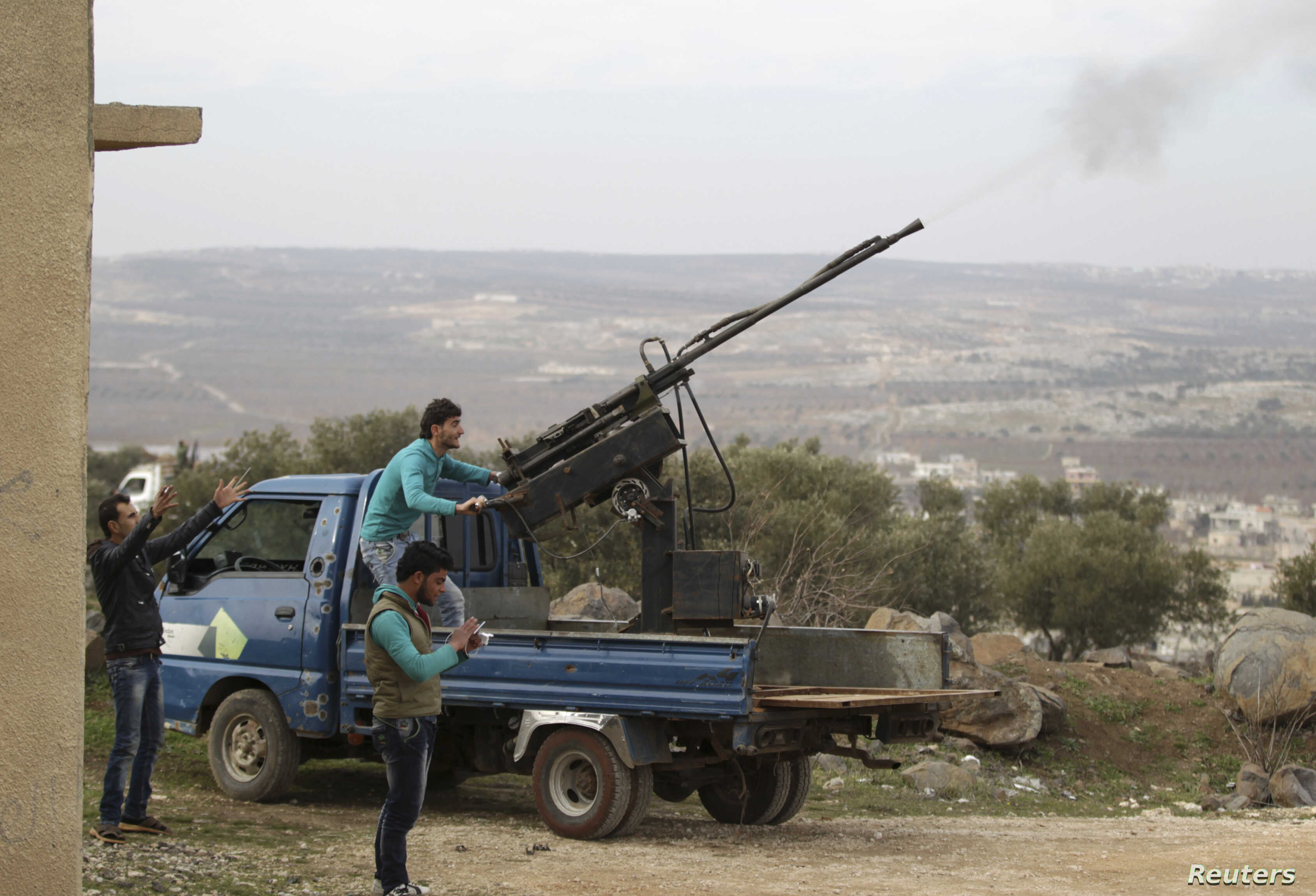 FILE - A rebel fighter from the Ahrar al-Sham Islamic Movement fires an anti-aircraft weapon towards what they said was a helicopter belonging to forces loyal to Syria's President Bashar al-Assad in Jabal al-Zawiya in the southern countryside of Idli...