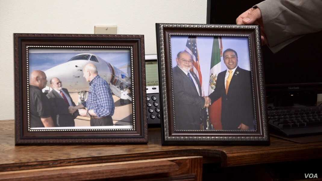 Nogales, Arizona mayor John Doyle displays a photo taken of himself and his Nogales, Mexico counterpart in his office. To the left is a photo taken with U.S. Secretary of Homeland Security John Kelly.  (Photo: R. Taylor/VOA)