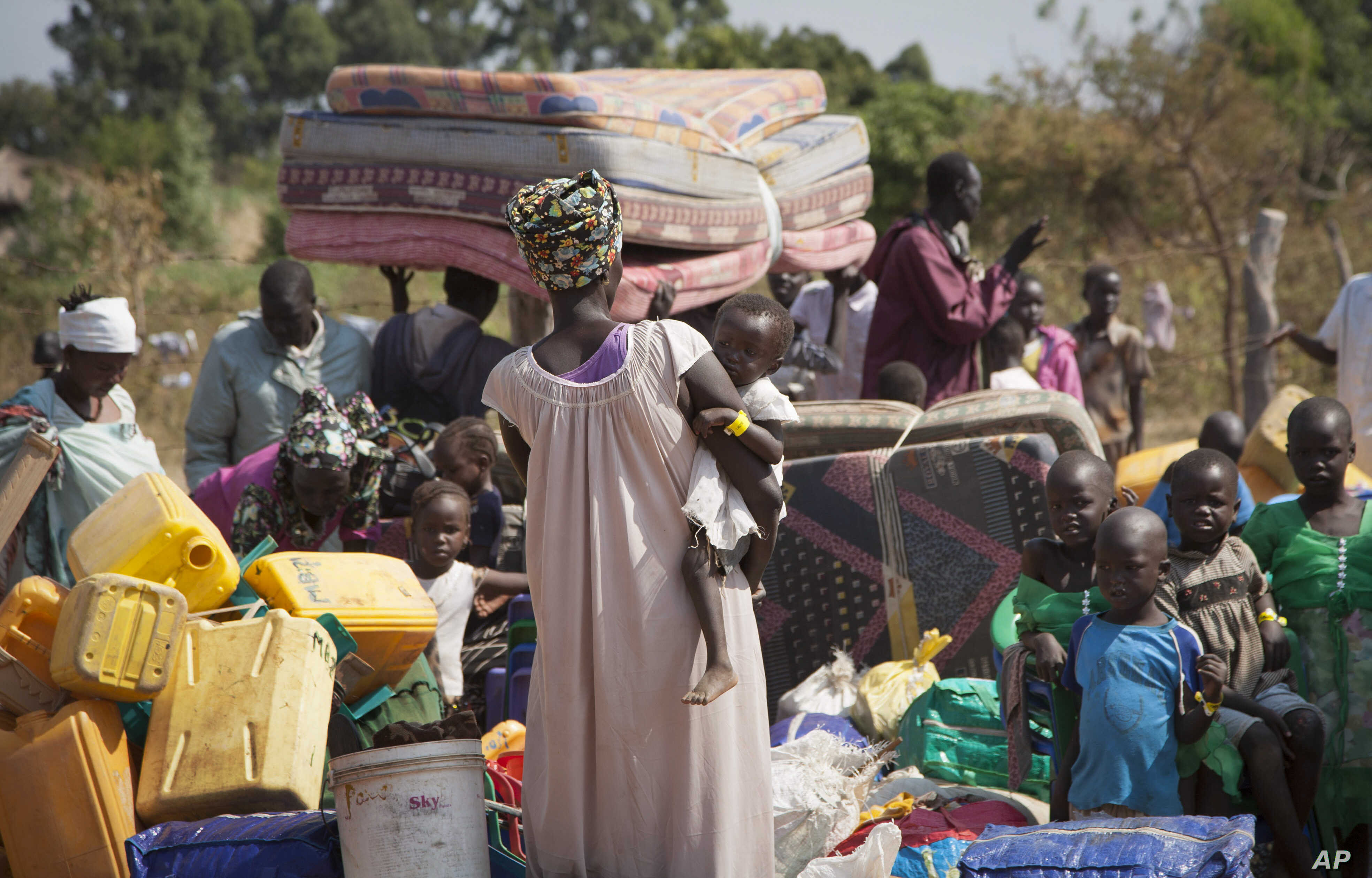 FILE - Refugees who fled the recent violence in South Sudan and crossed the border into Uganda carry their belongings as they await transportation from a transit center in the town of Koboko to a nearby settlement in Arua District, in northern Uganda...