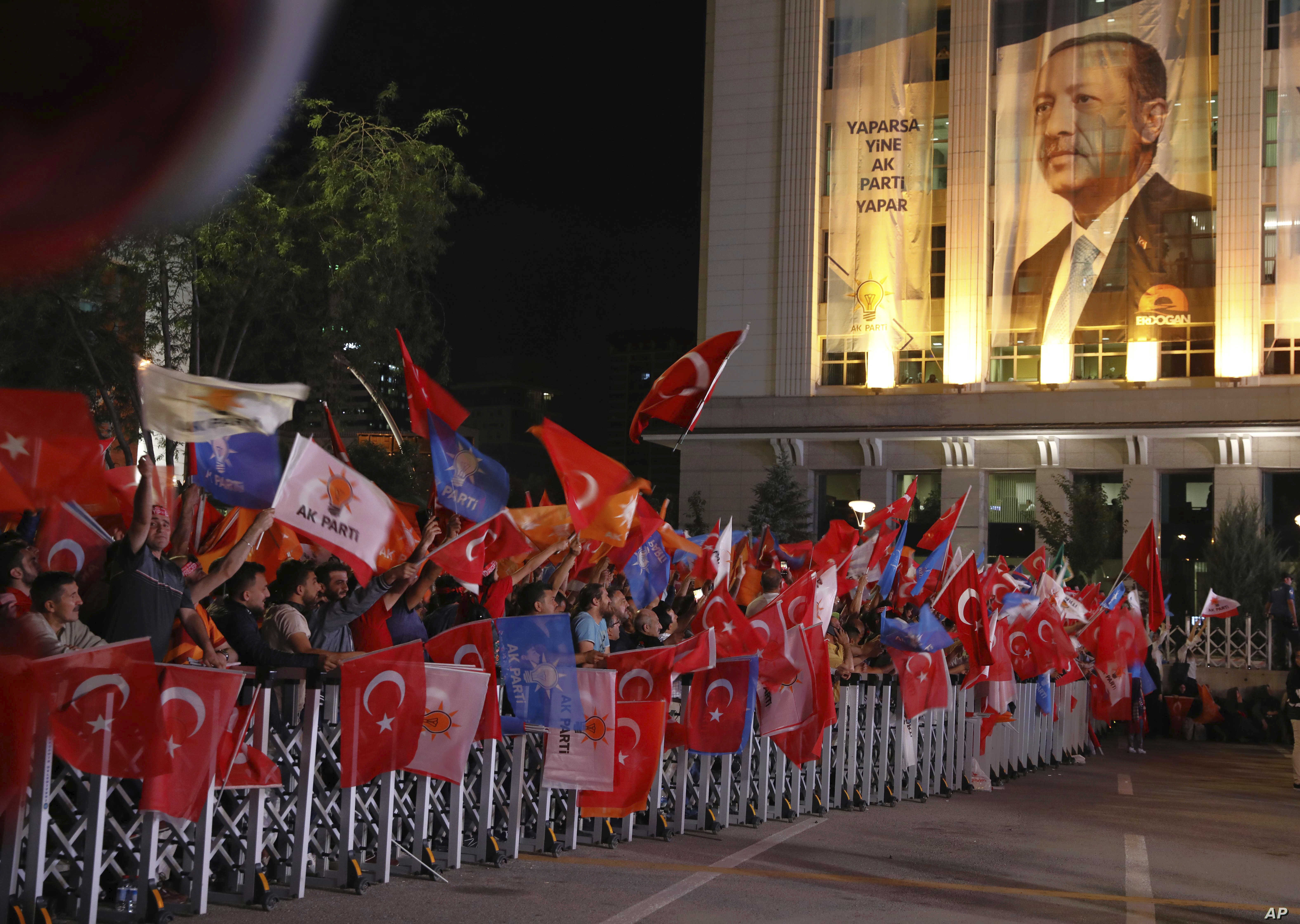 Supporters of Turkey's President and leader of ruling Justice and Development Party Recep Tayyip Erdogan celebrate outside his party's headquarters in Ankara, Turkey, late Sunday, June 24, 2018.