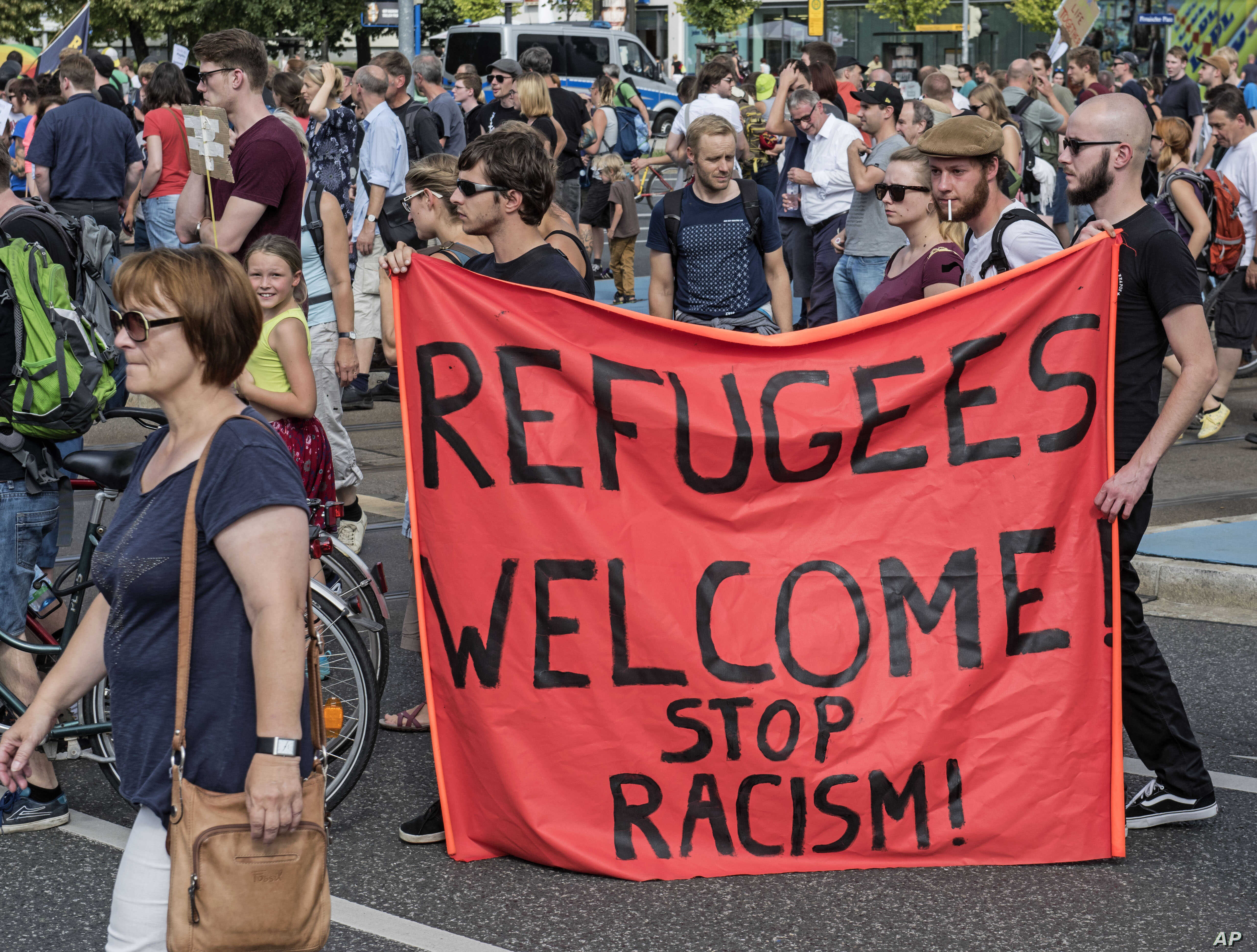 Protesters  demonstrate   with a banner 'Refugees welcome!' in Dresden, eastern Germany, Aug. 29, 2015. A refugee shelter was attacked by far-right protesters in Heidenau near Dresden over the last weekend.