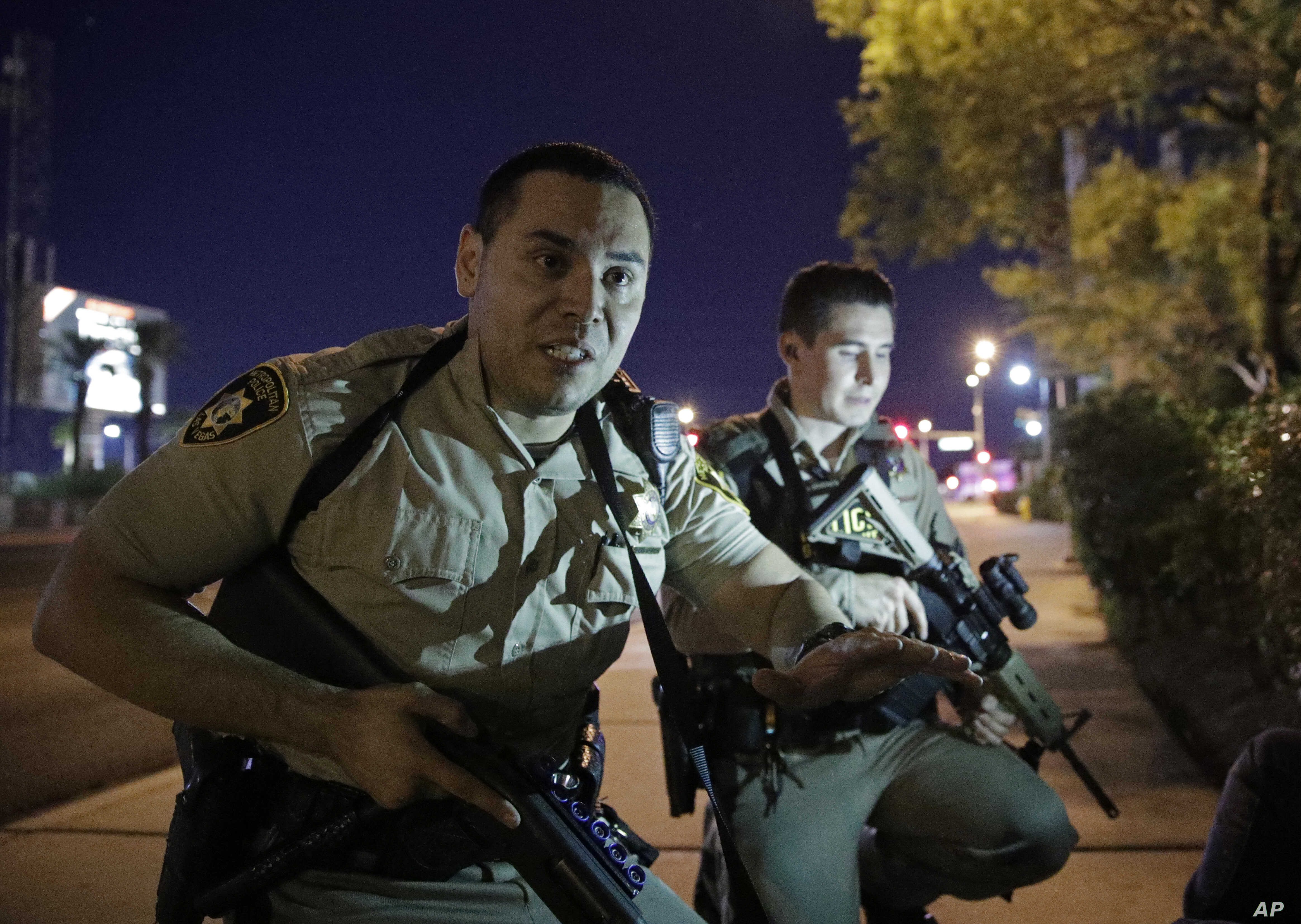Police officers advise people to take cover near the scene of a shooting near the Mandalay Bay resort and casino on the Las Vegas Strip, Sunday, Oct. 1, 2017, in Las Vegas.