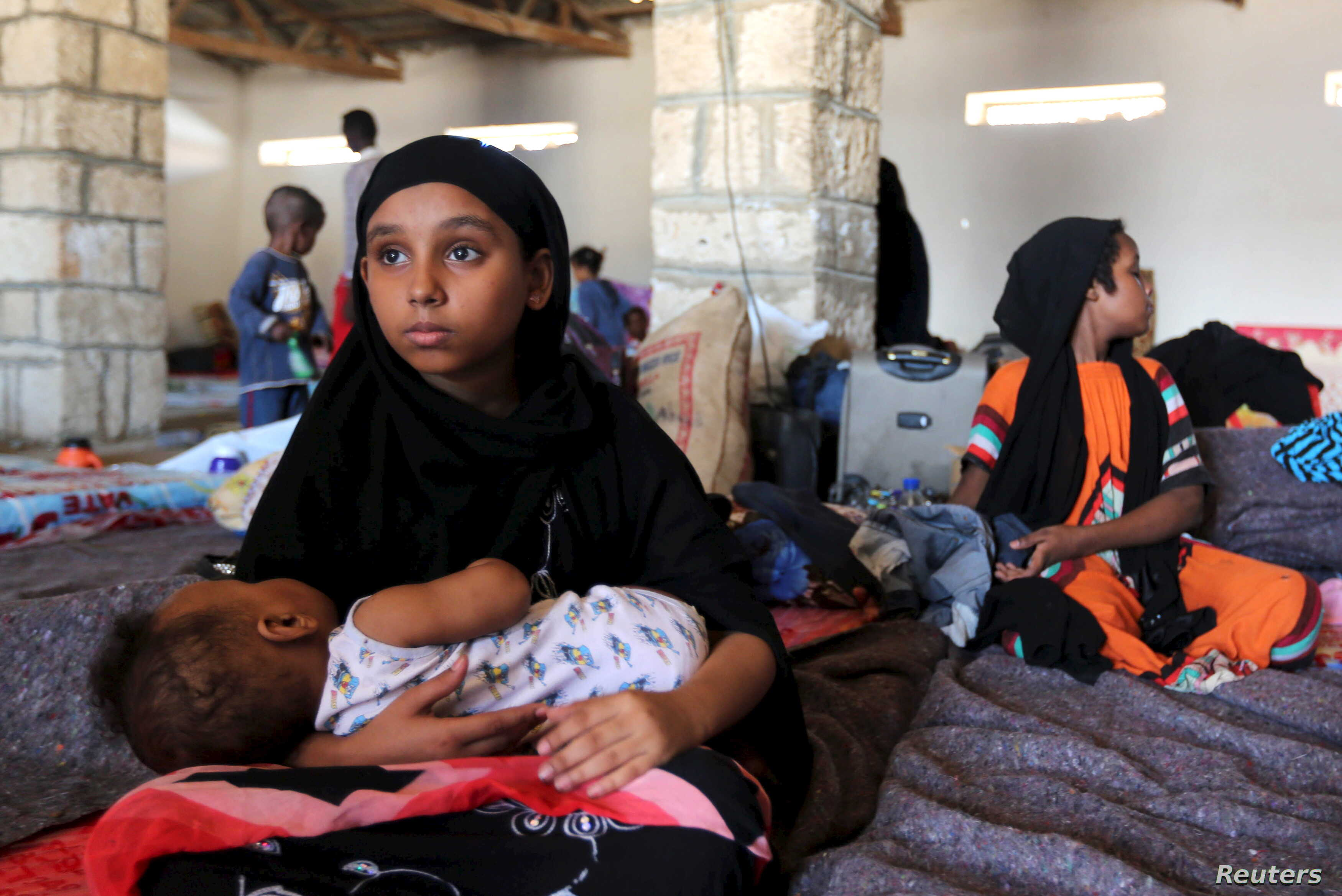 A Yemeni refugee cradles a baby in a temporary shelter in Bosasso, a port town in Somalia's Puntland, April 17, 2015.