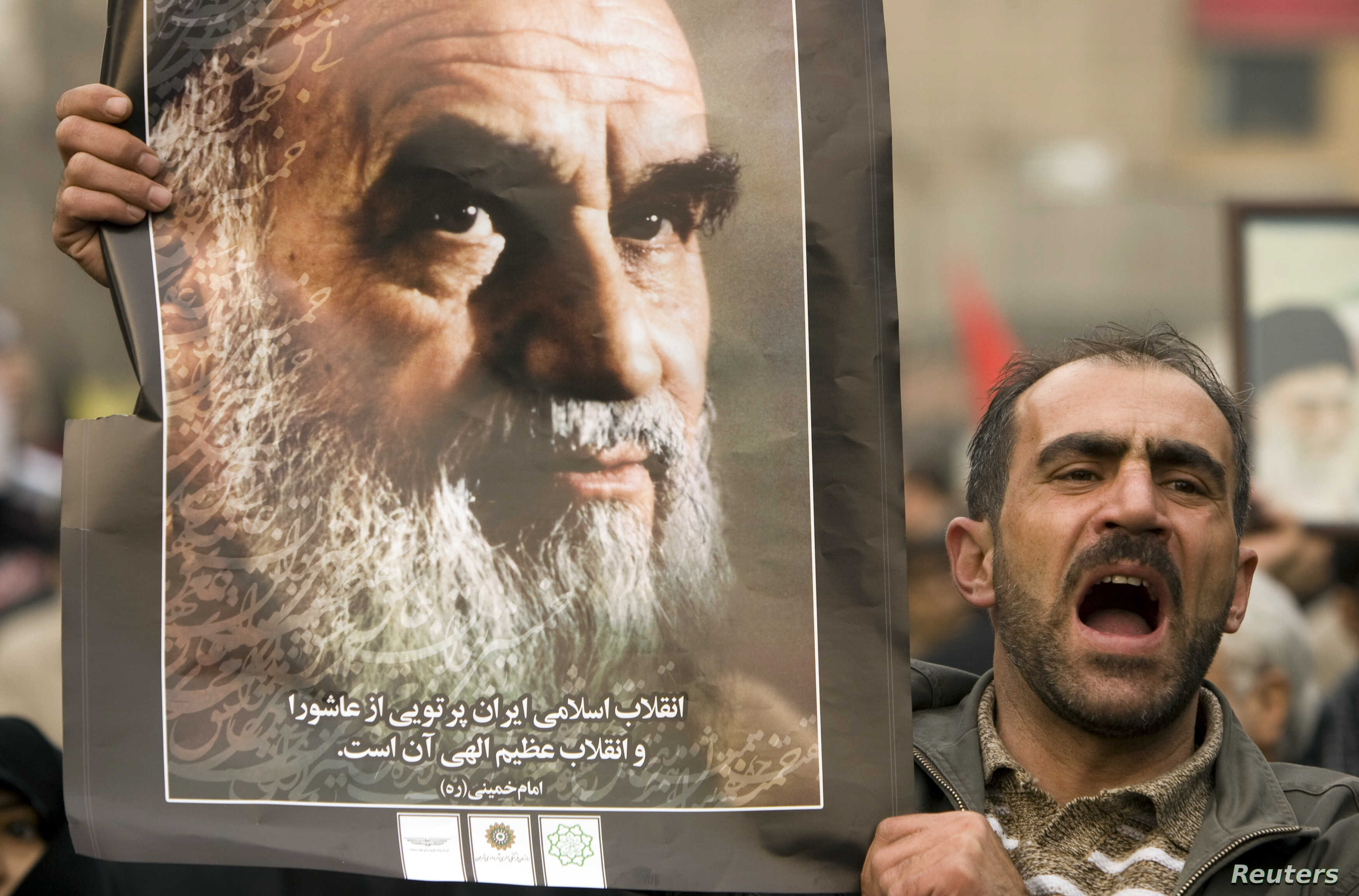 FILE - A man holds a picture of Ayatollah Ruhollah Khomeini, founder of the Islamic Republic as government supporters protest against opposition demonstrations during the holy day of Ashura, in Tehran, Dec. 30 2009.