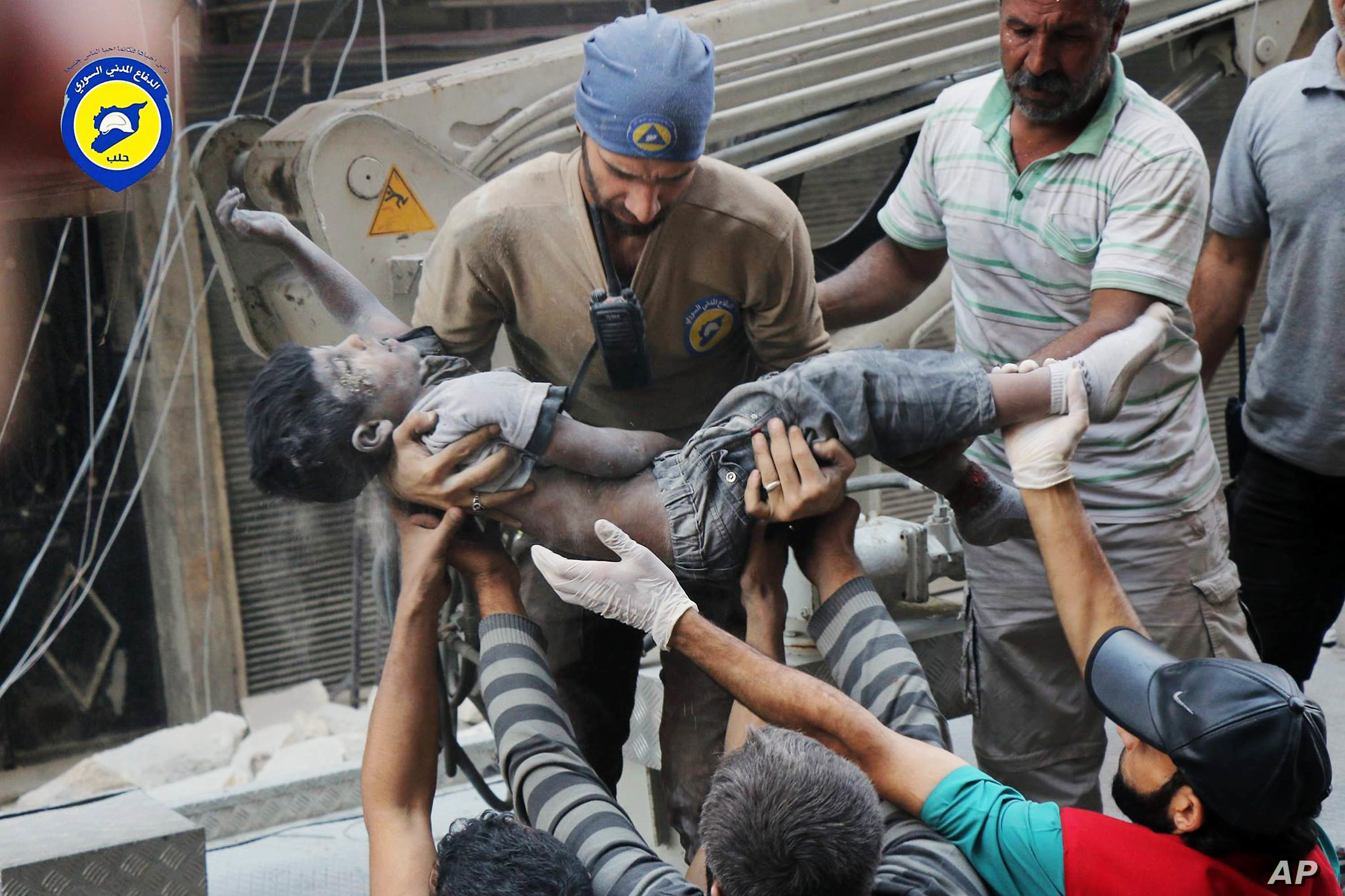 Sept. 27, 2016 photo, provided by the Syrian Civil Defense group known as the White Helmets, shows a Civil Defense worker carrying the body of a child after airstrikes hit al-Shaar neighborhood in Aleppo, Syria.