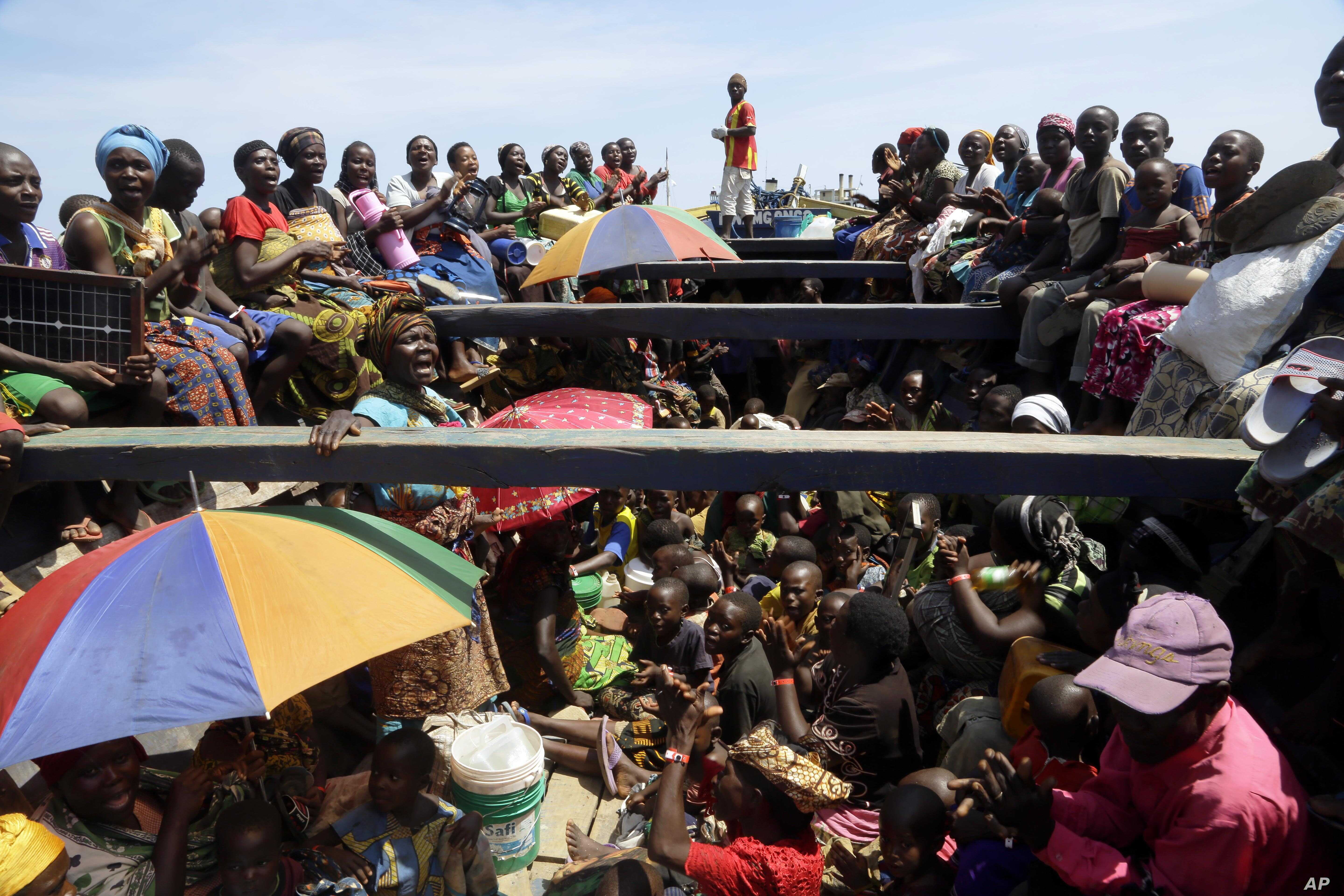 FILE - Refugees who fled Burundi's violence and political tension sing in a speedboat taking them to a ship freighted by the U.N., at Kagunga on Lake Tanganyika, Tanzania, May 23, 2015, to be taken to the port city of Kigoma.