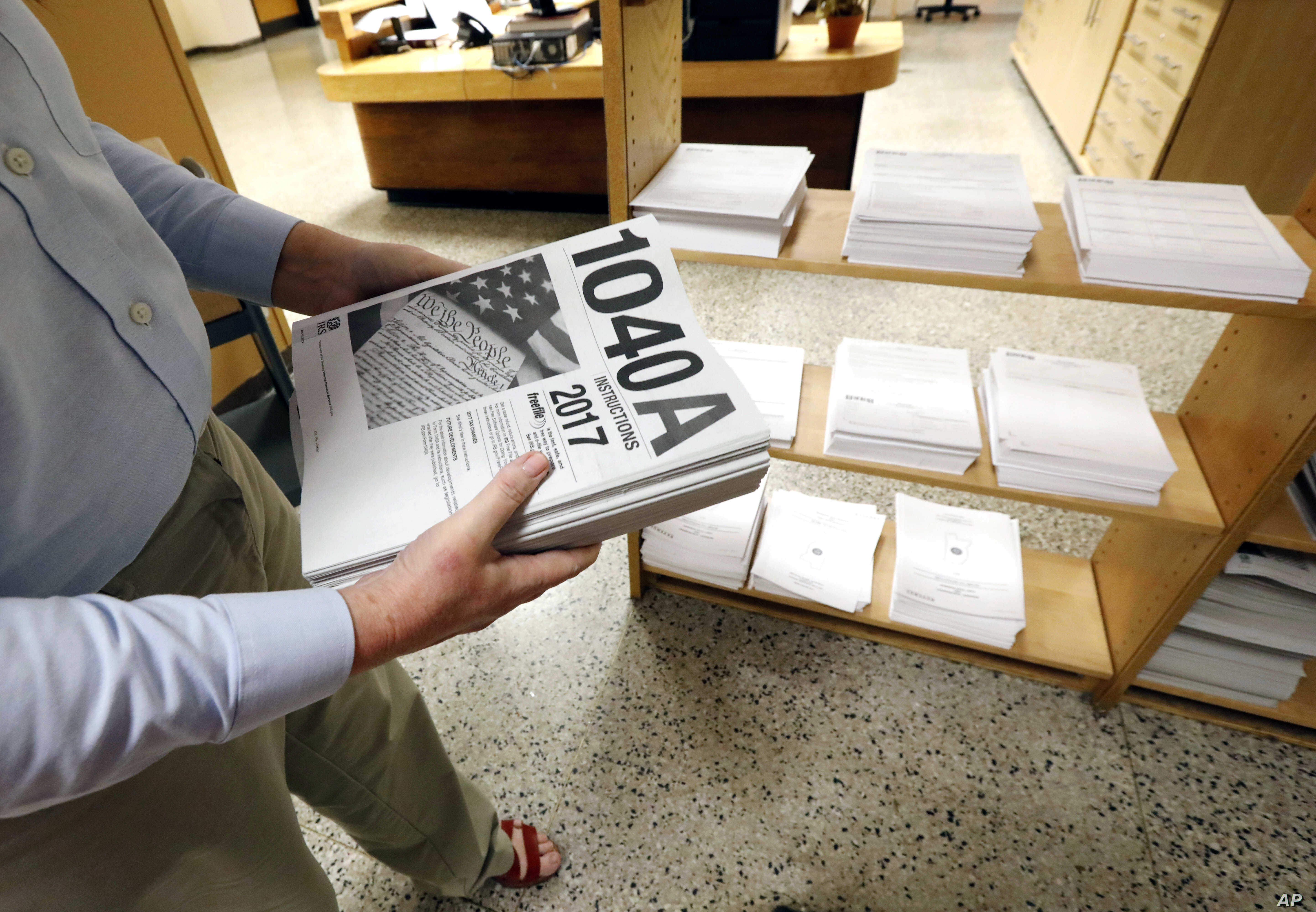 FILE - A worker adds federal tax filing information to shelves at the Eudora Welty Library in Jackson, Miss., Feb. 15, 2018.