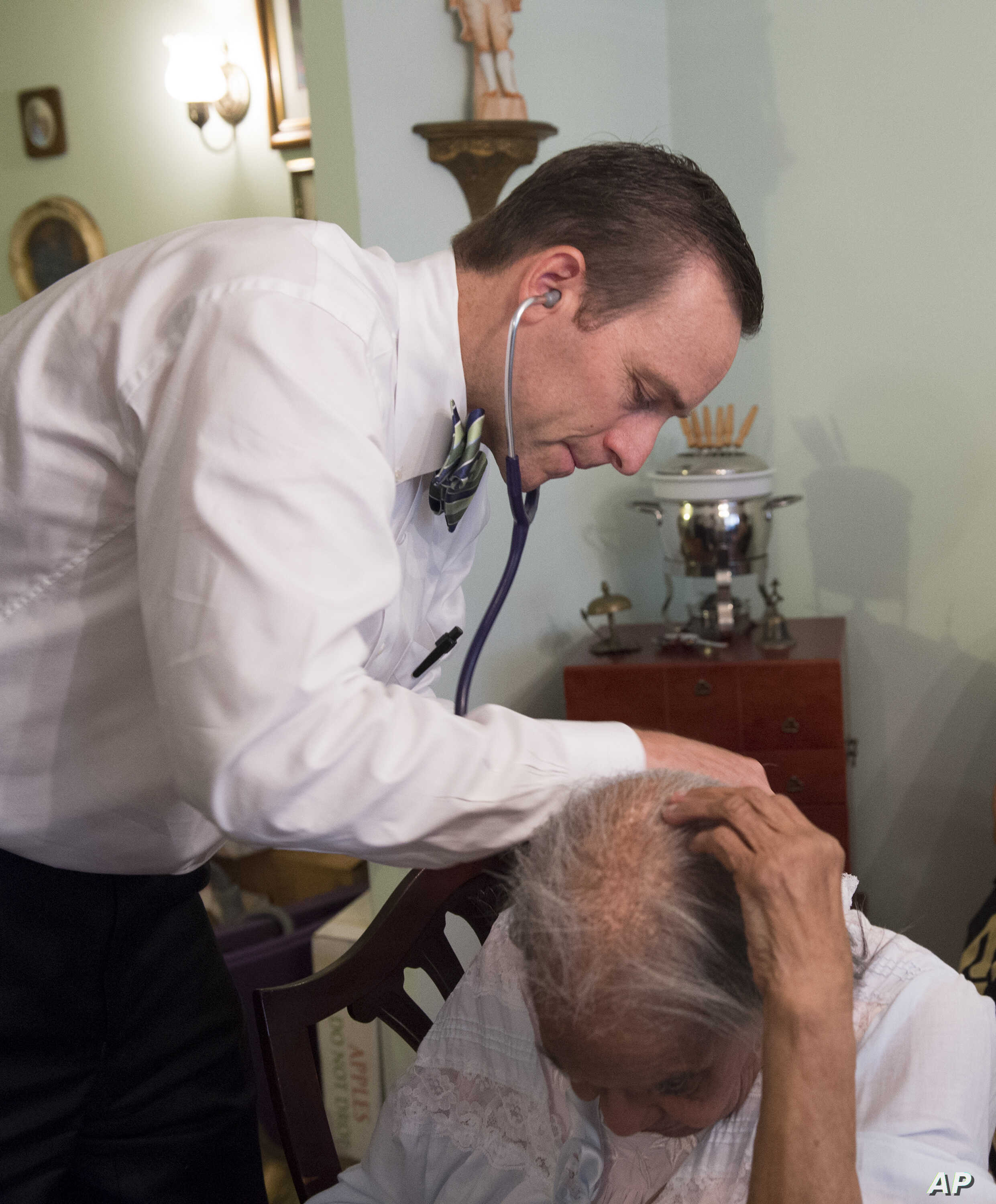 FILE - Dr. Eric De Jonge of Washington Hospital Center conducts a Medicare examination of a patient during a house call at her home in Washington, Aug. 7, 2014.