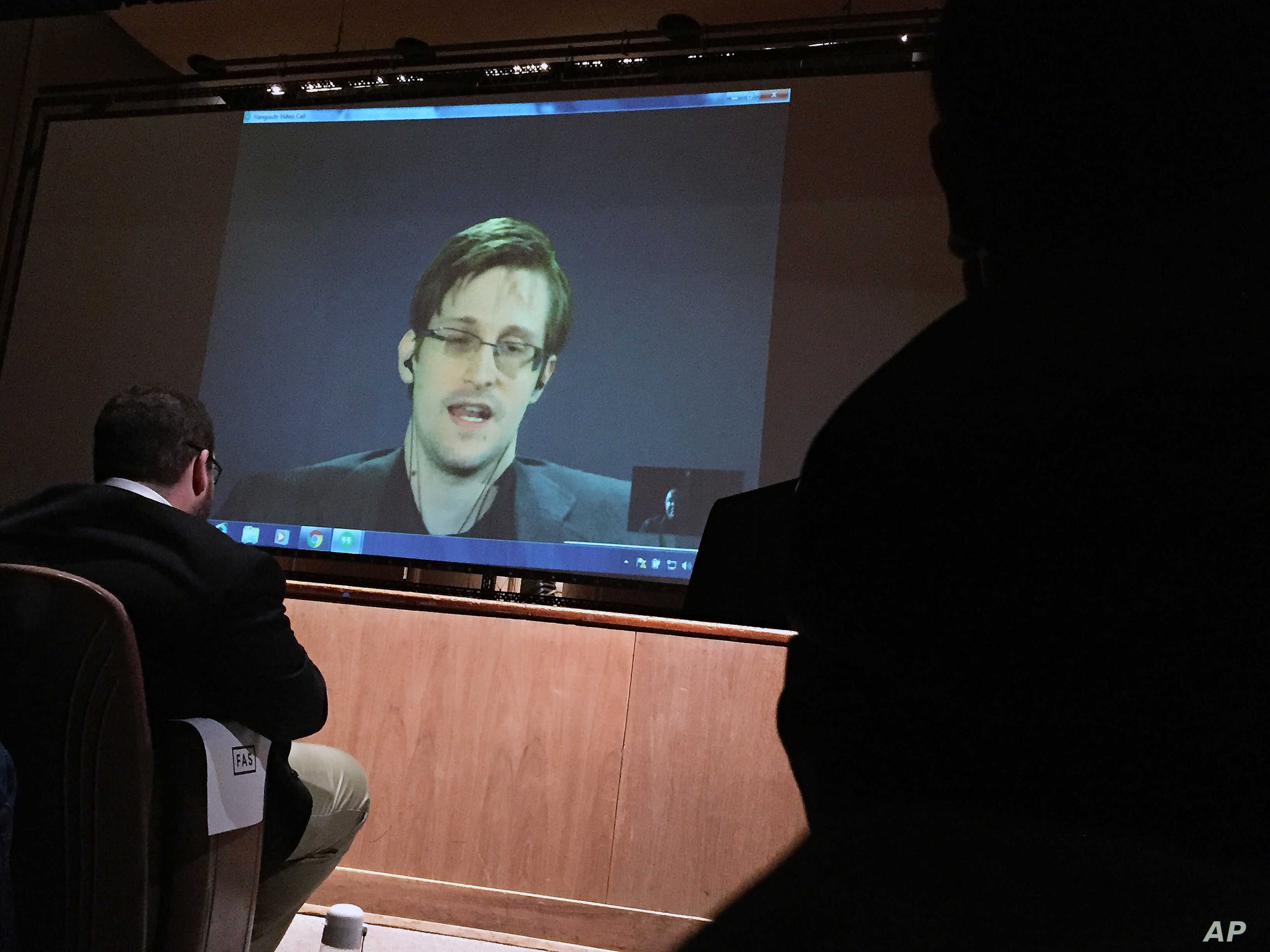 Former National Security Agency contractor Edward Snowden, center speaks via video conference to people in the Johns Hopkins University auditorium in Baltimore, Feb. 17, 2016.