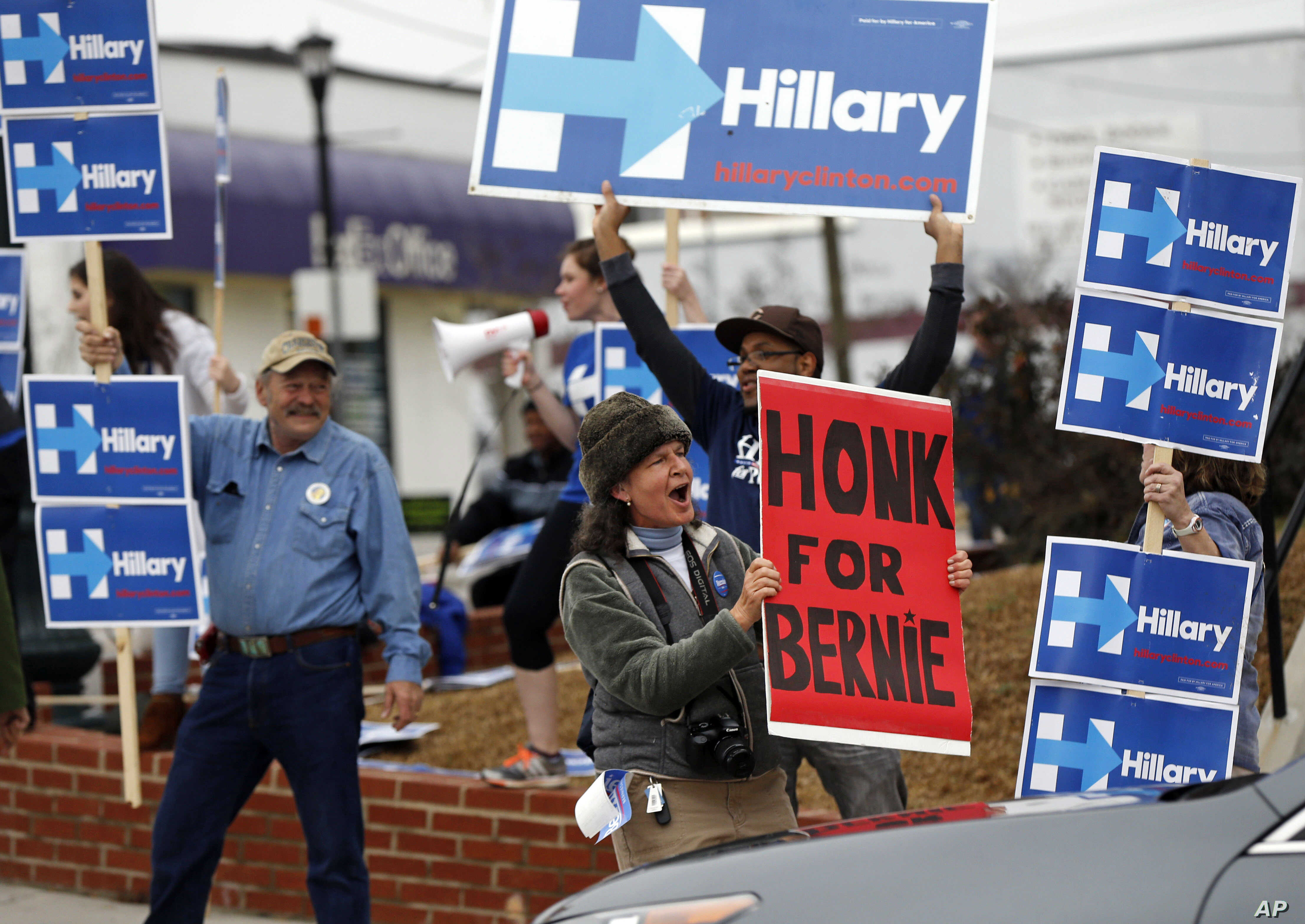 FILE - A Sen. Bernie Sanders supporter cheers for passing motorists to honk, amongst a group of Hillary Clinton backers outside the University of South Carolina School of Law in this Feb. 23, 2016 photo.