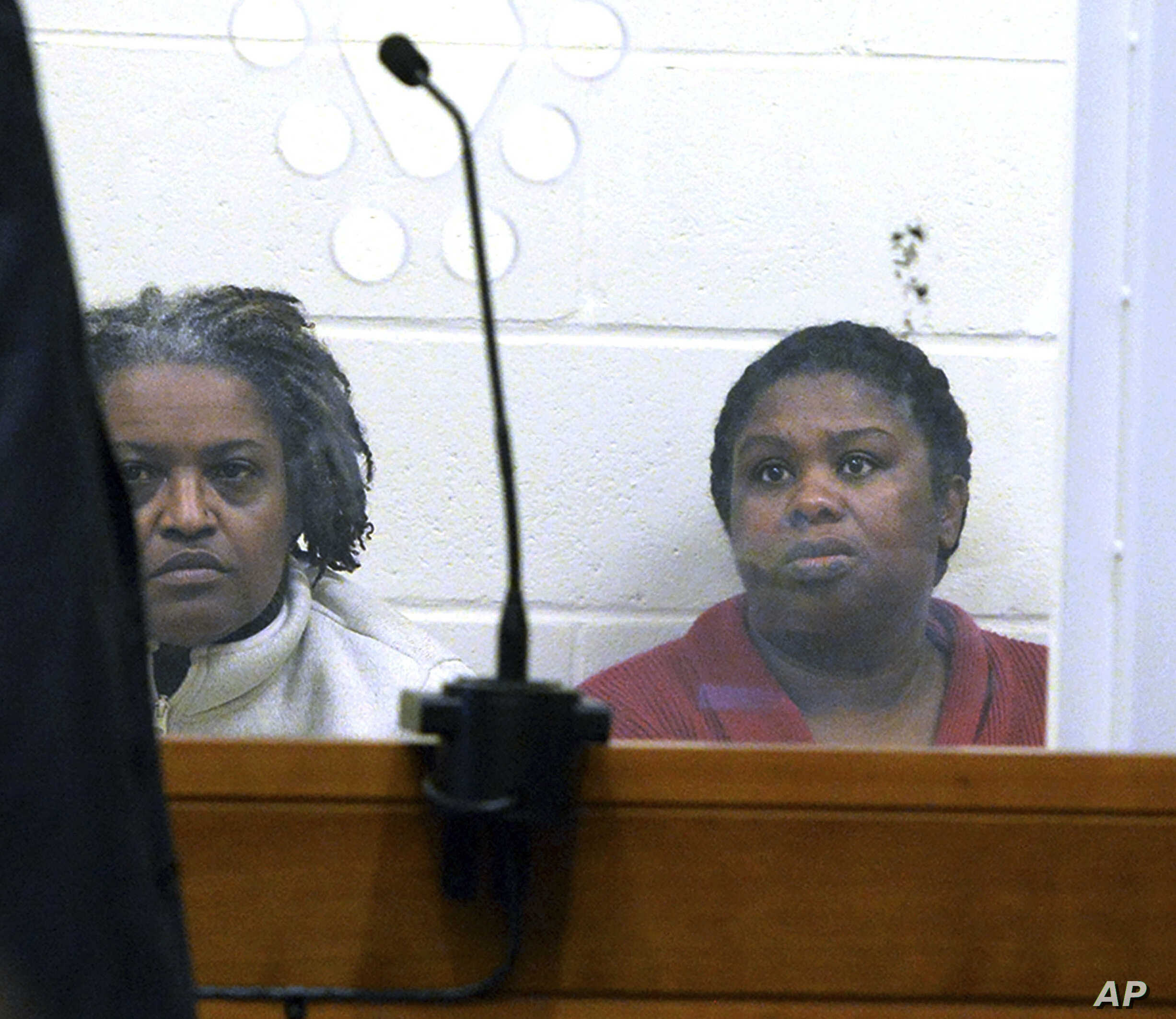 FILE - In this Feb. 1, 2018 file photo, sisters Rachel Hilaire and Peggy LaBossiere sit in Brockton District Court in Bridgewater, Mass., charged with tying down and burning a 5-year-old girl, permanently disfiguring her, in a voodoo ritual meant to ...