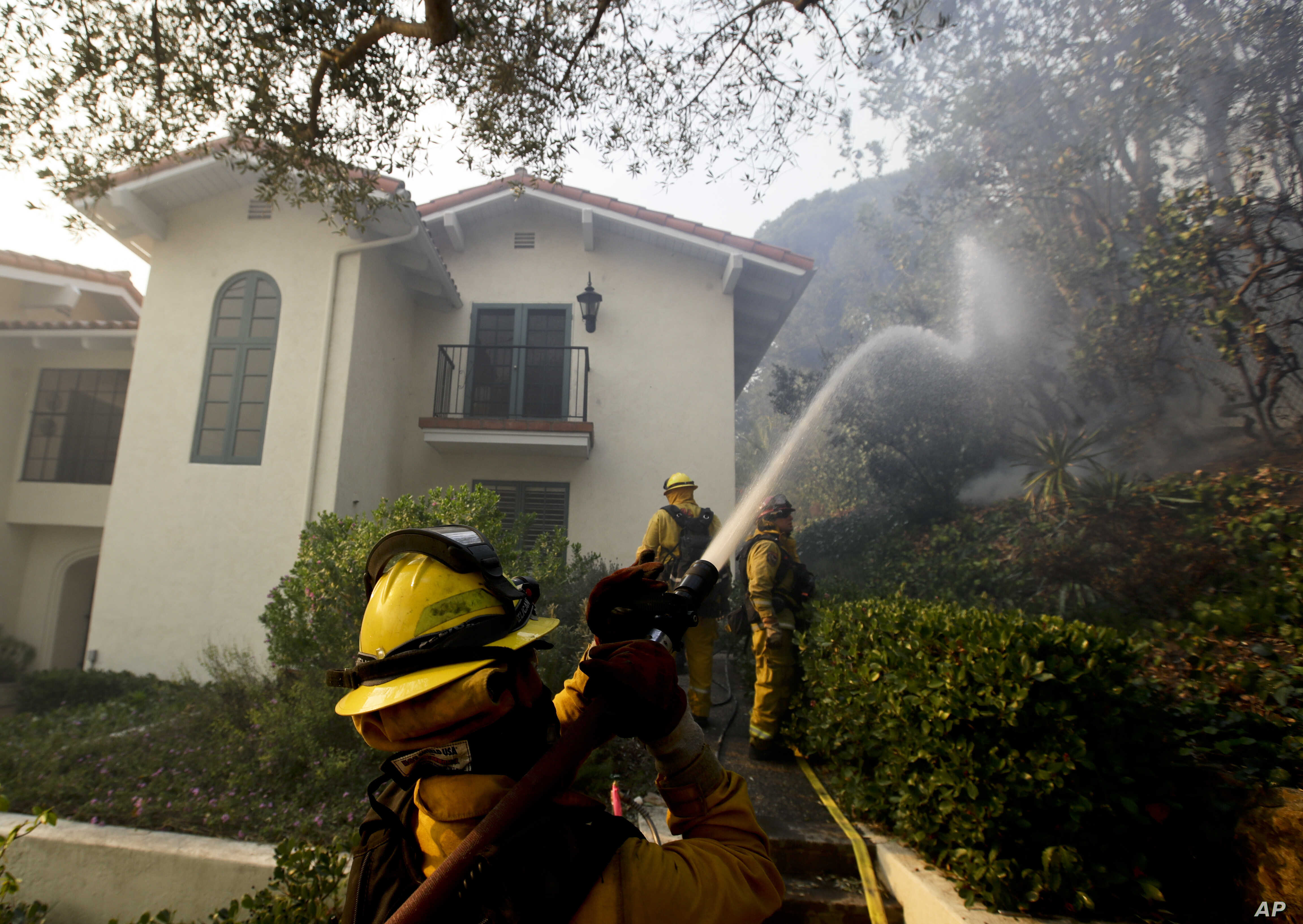 Firefighters from Kern County, Calif., work to put out hot spots, Dec. 16, 2017, in Montecito, Calif.