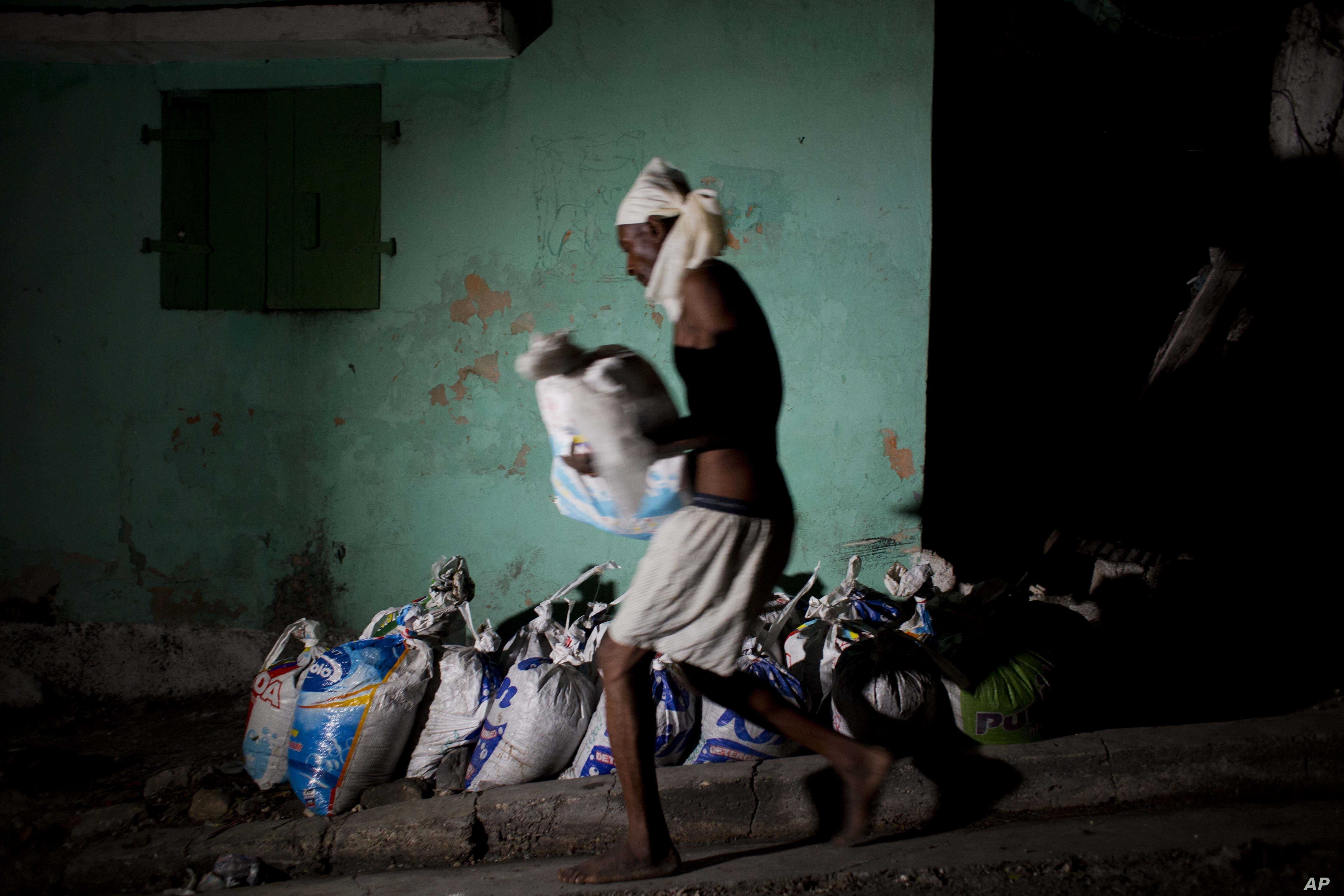 """FILE - A """"bayakou,"""" or human waste cleaner, carries a sack filled with human waste to be hauled away and dumped before sunrise, in Port-au-Prince, Haiti, Dec. 22, 2016."""