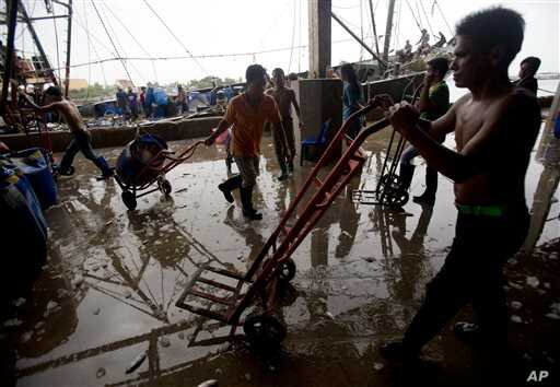 Migrant workers unload frozen fish from a boat at a fish market in Samut Sakhon Province, west of Bangkok, Friday, June 20, 2014. The United States had blacklisted Thailand and Malaysia for failing to meet its minimum standards in fighting human traf...