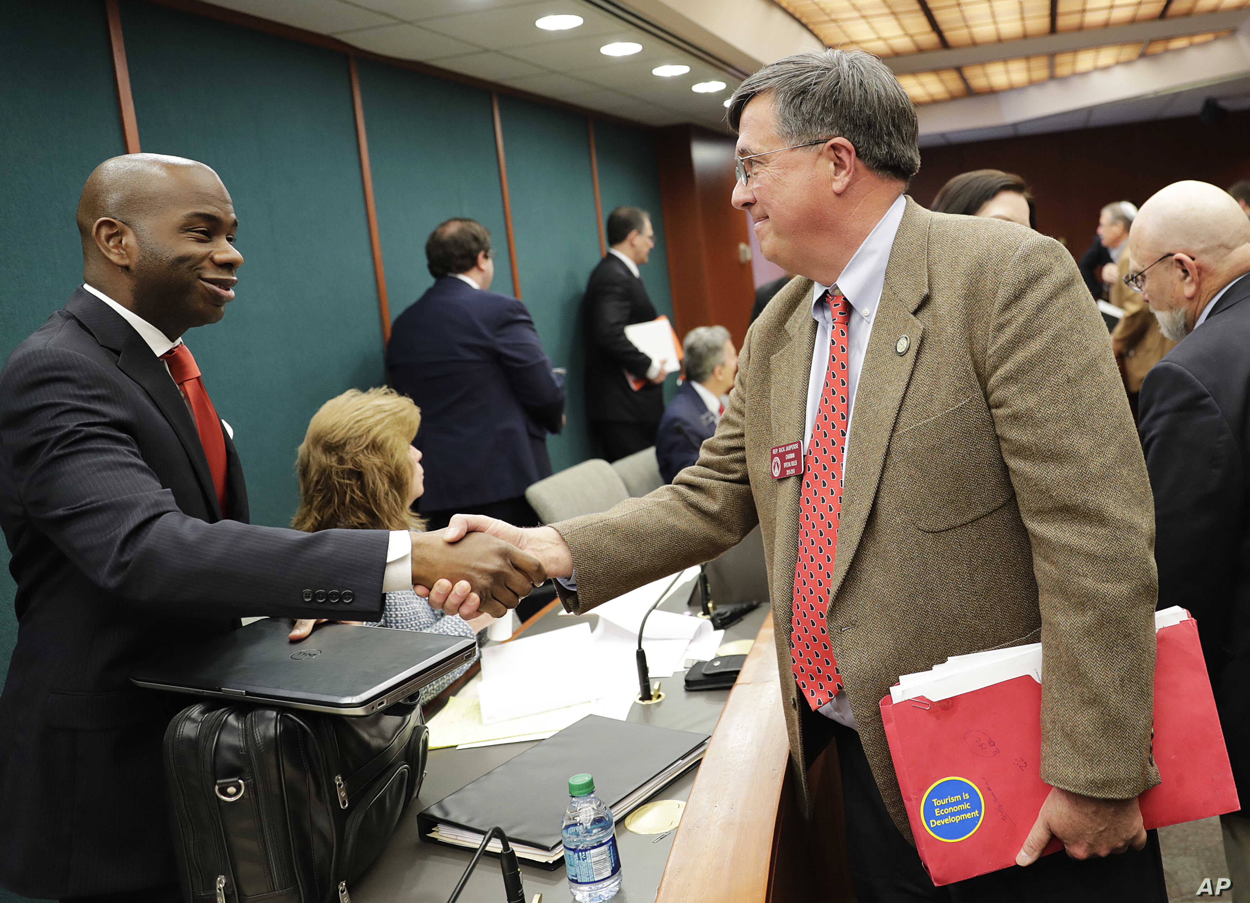 Georgia state Rep. Rick Jasperse, R-Jasper, right, shakes hands with Assistant Legislative Counsel Julius Tolbert in Atlanta after a Senate committee approved Jasperse's bill that would permit those with concealed carry weapons licenses to bring thei...