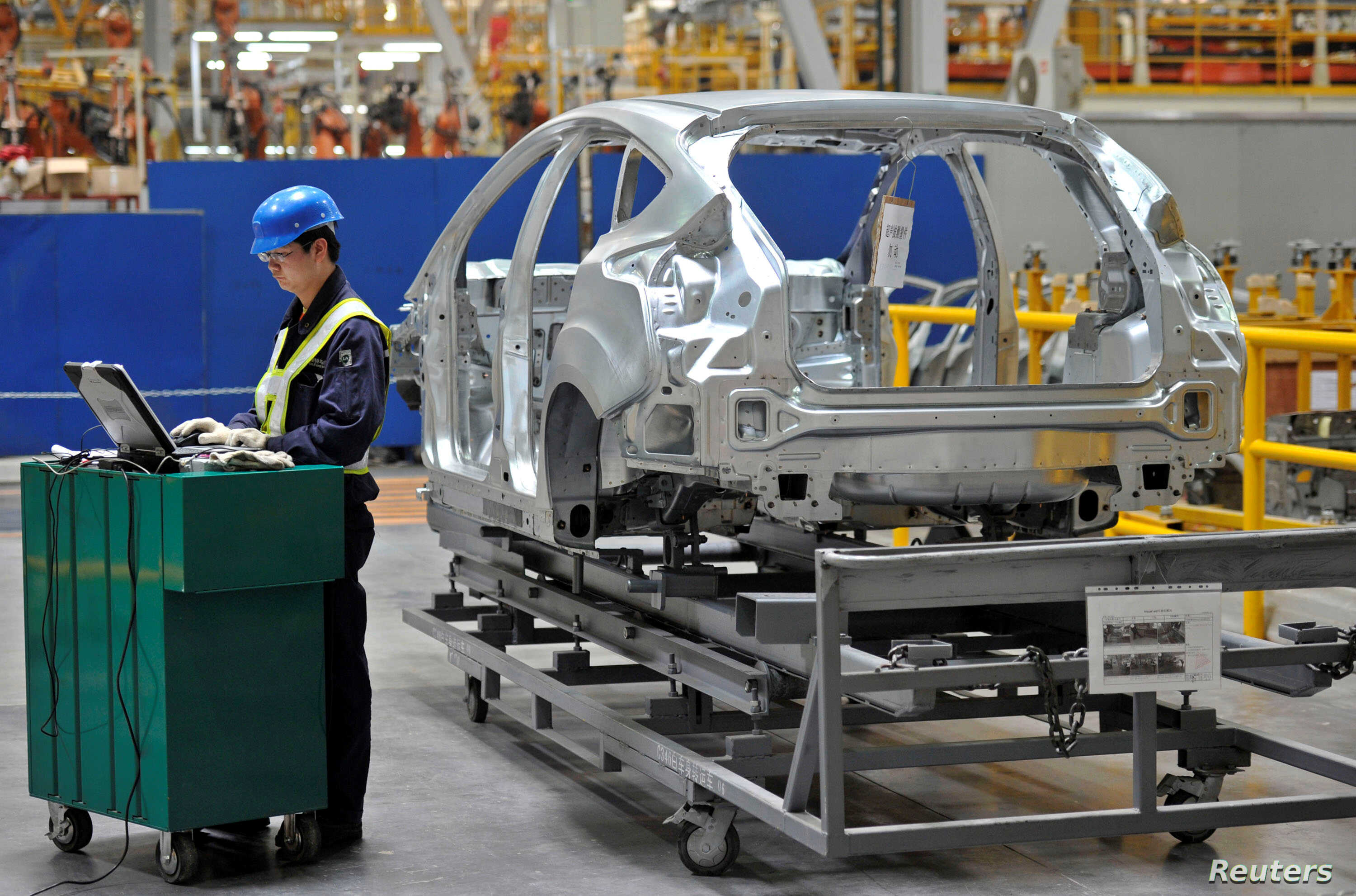 FILE - An employee uses a laptop next to a car body at an assembly line at a Ford manufacturing plant in Chongqing municipality, China.