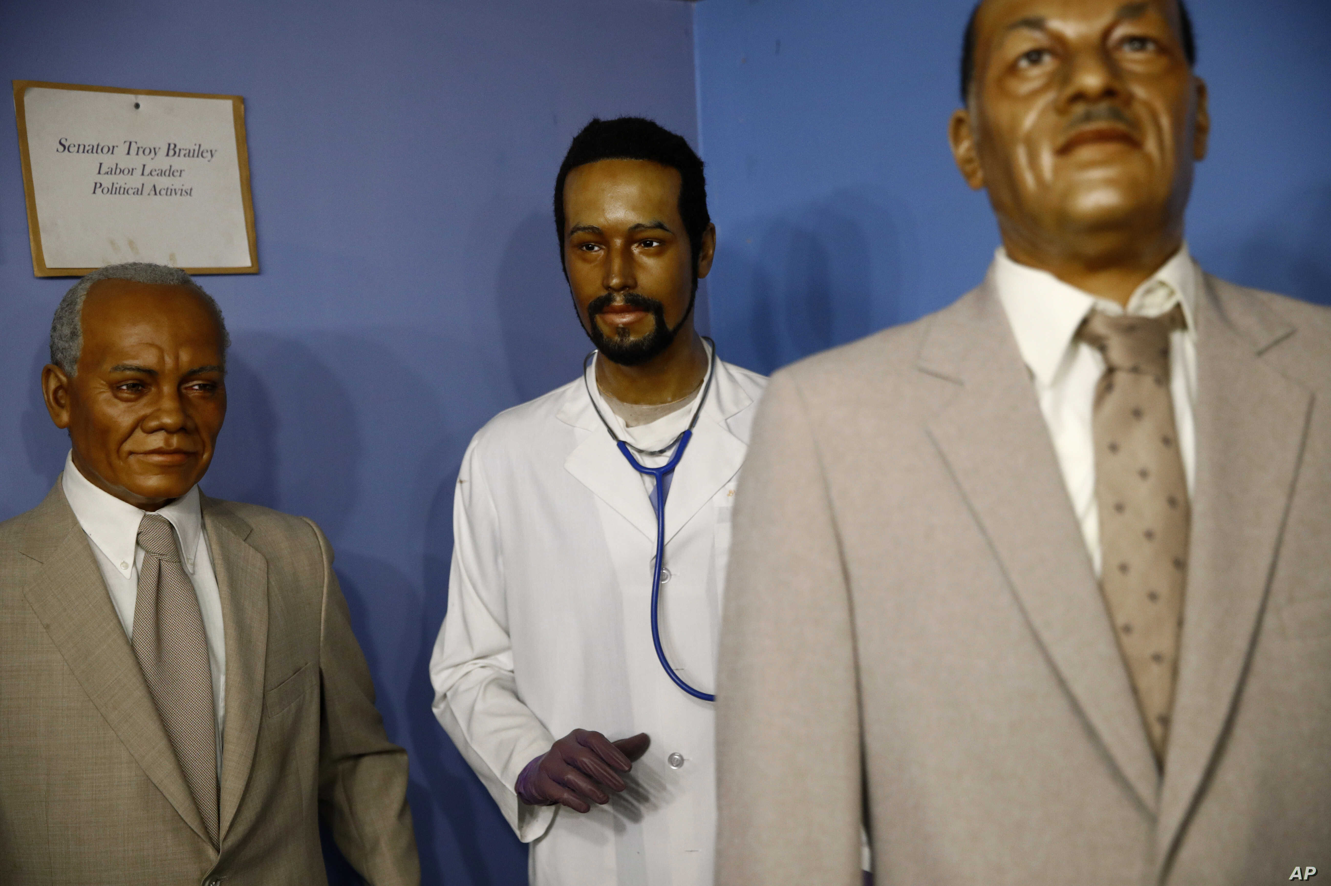 In this Aug. 15, 2018 photo, a wax figure depicting Department of Housing and Urban Development secretary Ben Carson, center, from his days as a neurosurgeon stands in a gallery at the National Great Blacks In Wax Museum in Baltimore.