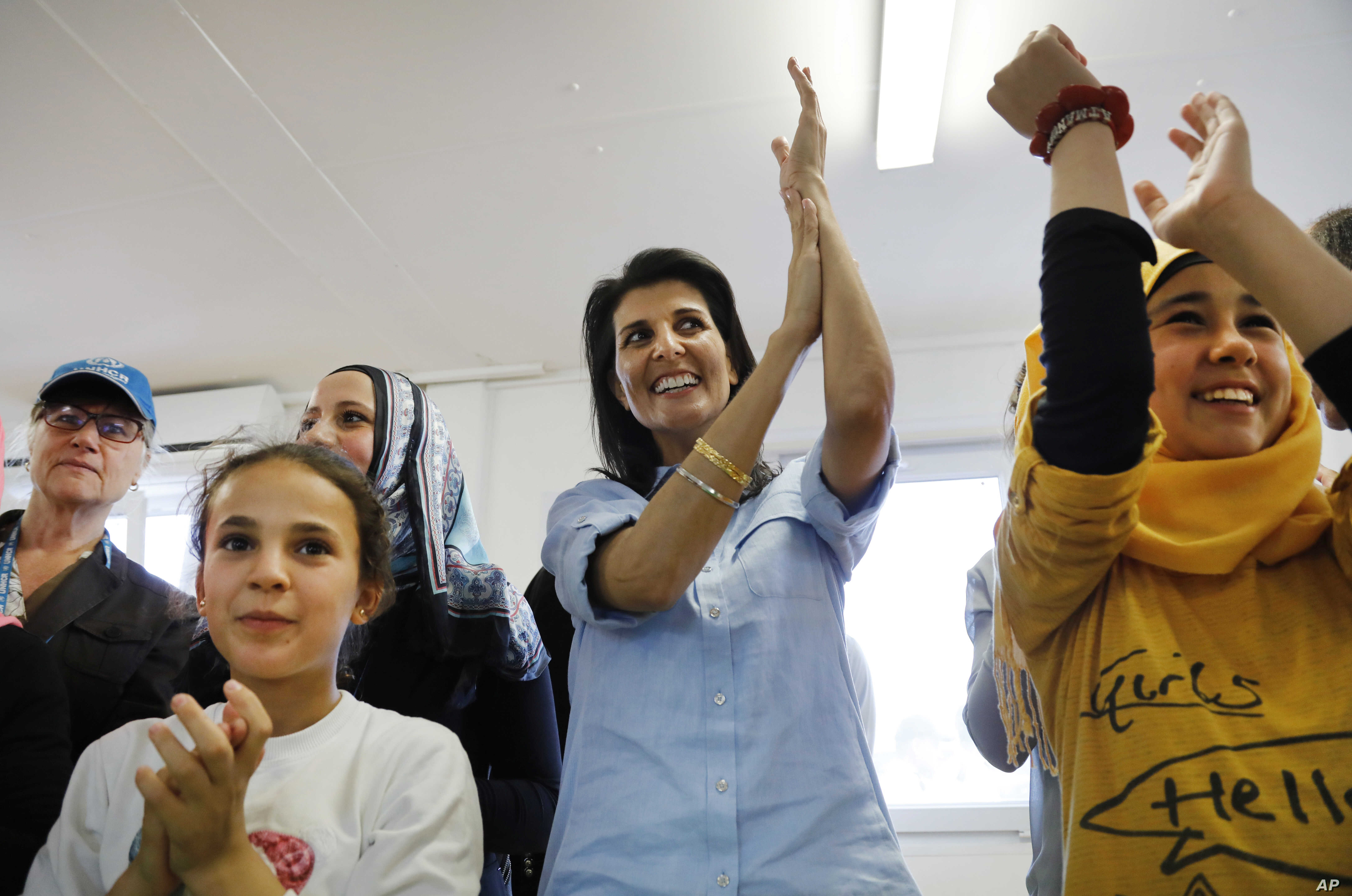 U.S. Ambassador to the U.N. Nikki Haley, center, sings and dances with Syrian refugee children during a visit at the Boynuyogun refugee camp near Hatay, southern Turkey, May 24, 2017.