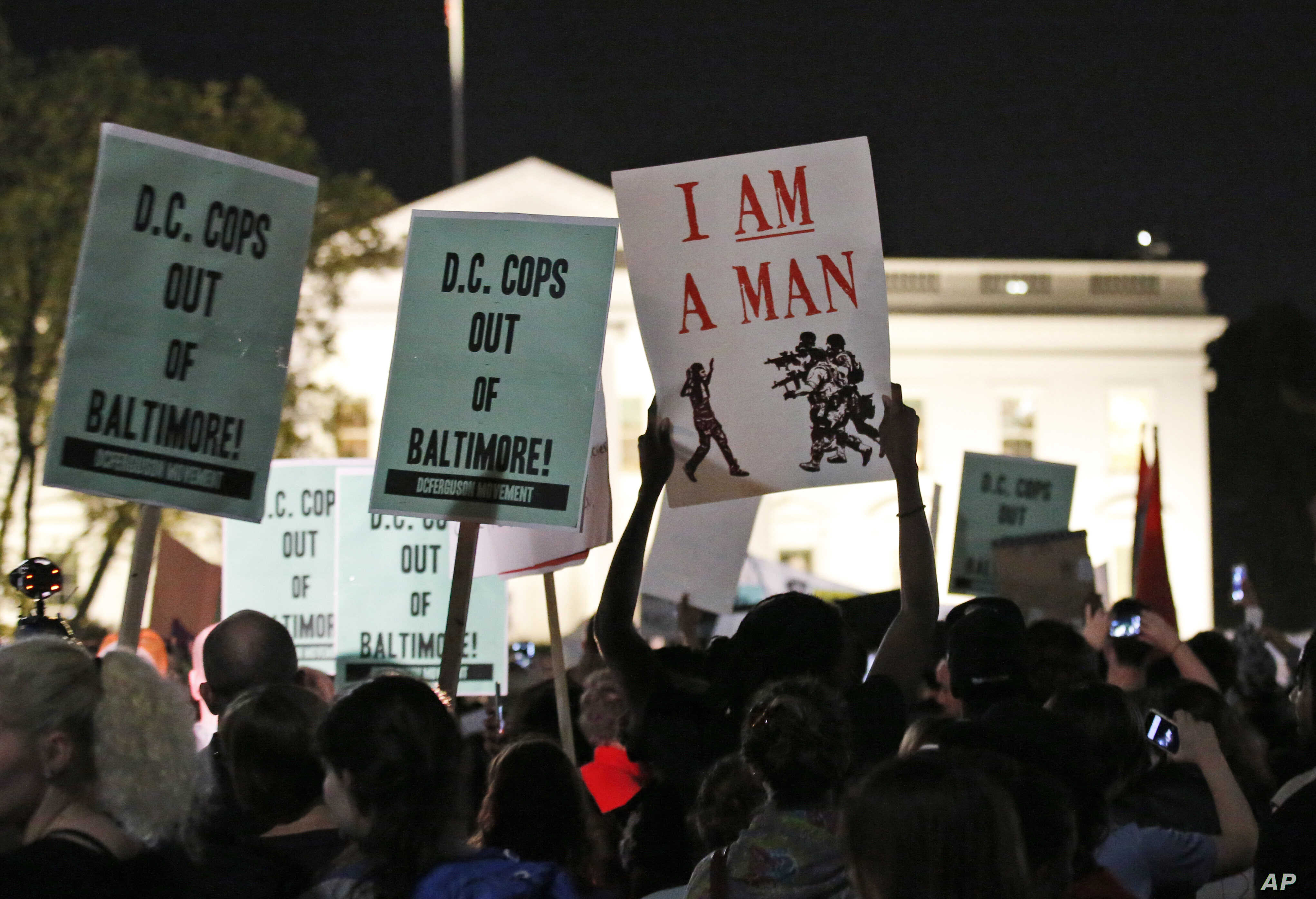Demonstrators hold signs during a protest to support the rallies in Baltimore, in front of the White House in Washington, April 29, 2015.