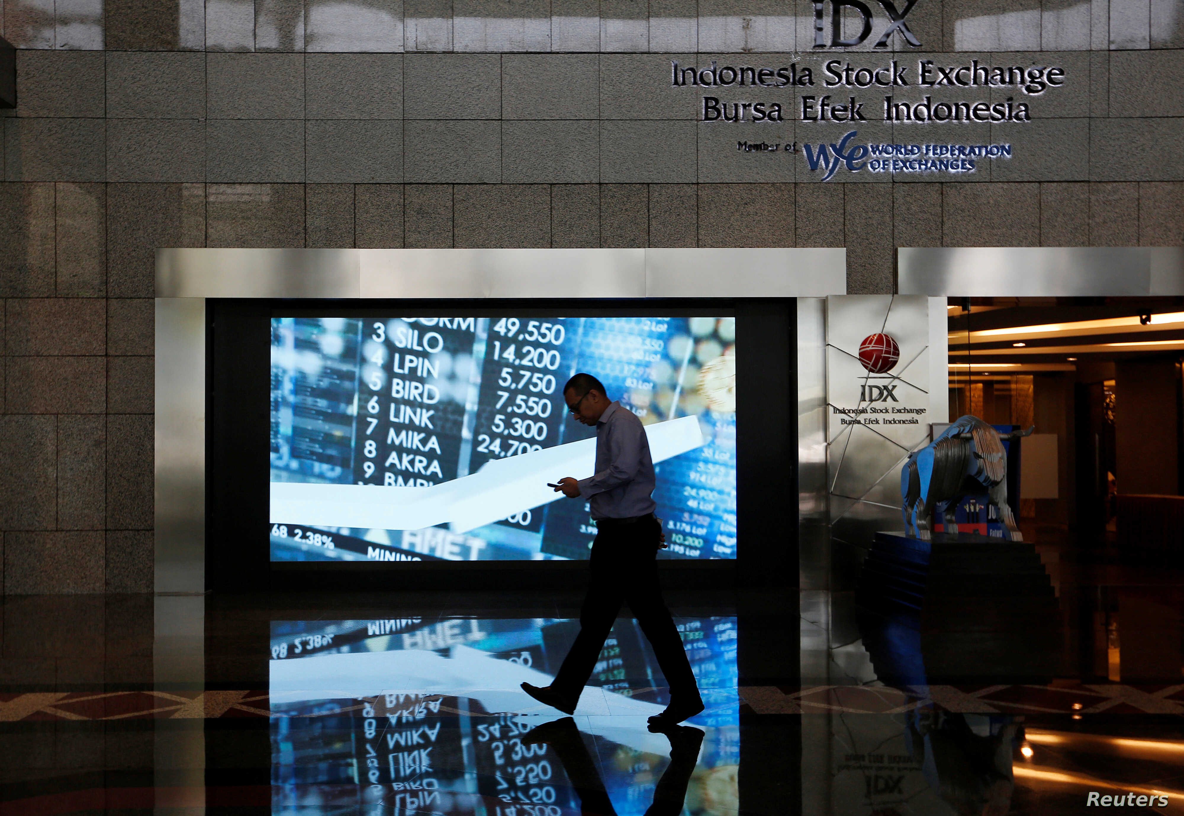 A man walks past screen at the Indonesia Stock Exchange building in Jakarta, Indonesia, Sept. 6, 2018.