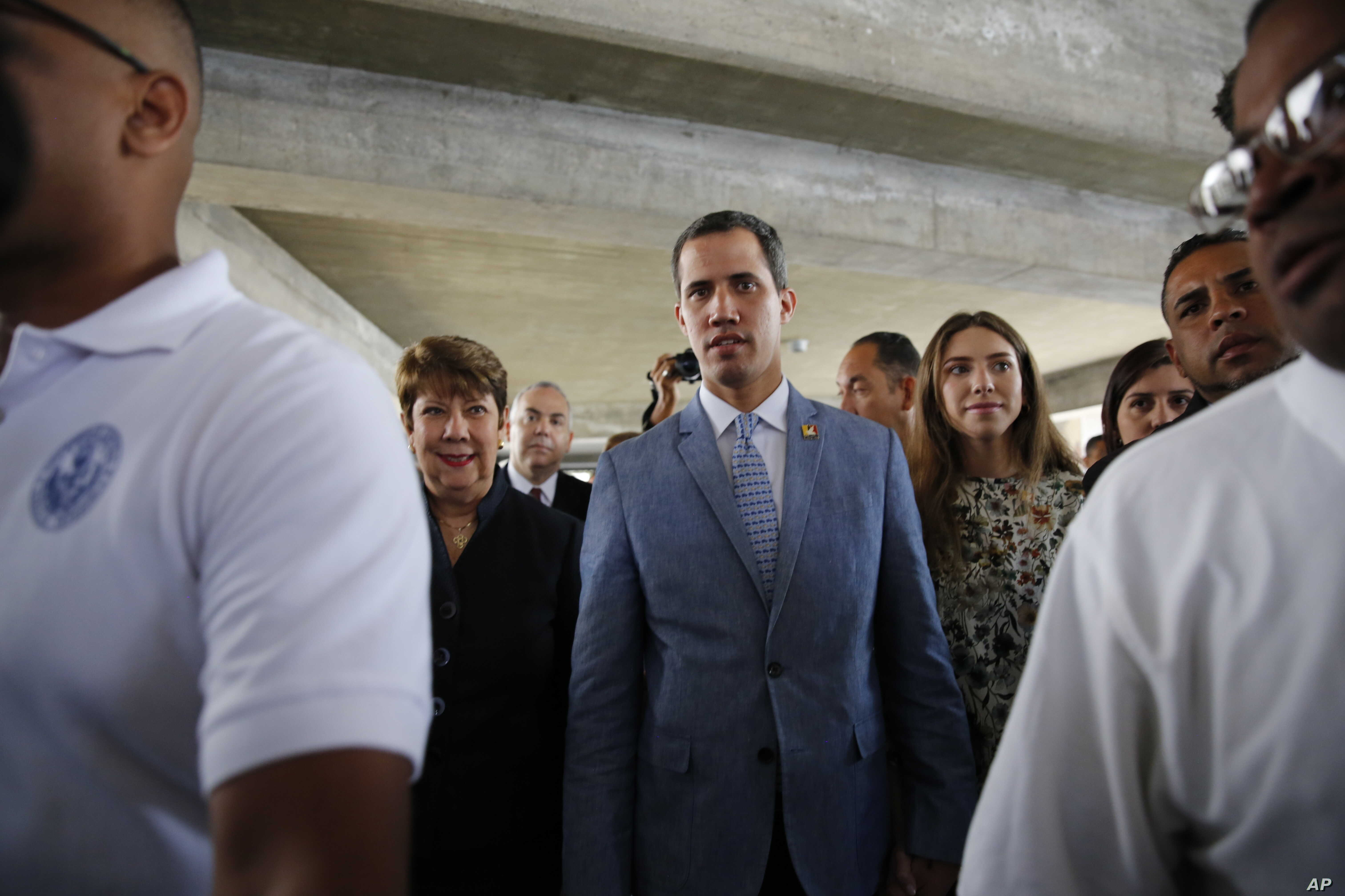 Accompanied by his wife Fabiana Rosales, center right, Venezuela's self proclaimed president Juan Guaido, arrives for a meet with university students at the Central University of Venezuela, in Caracas, Venezuela, Friday, Feb. 9, 2019.