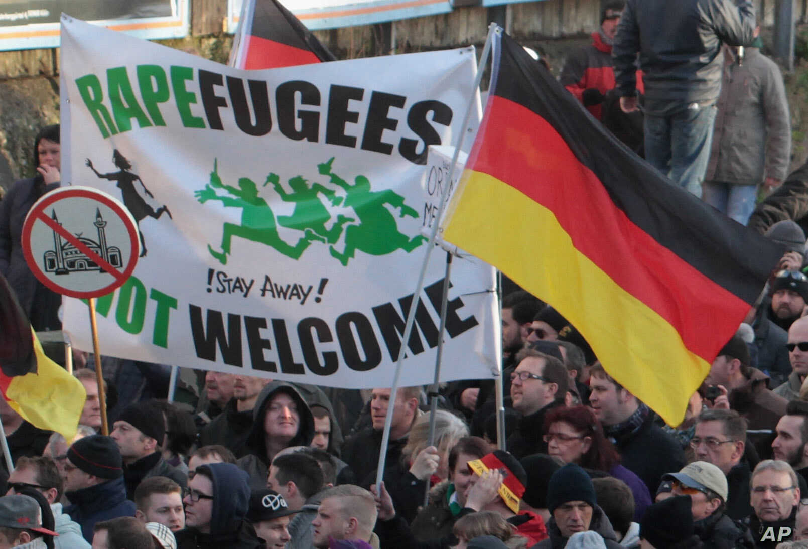 """Right-wing demonstrators hold a sign """"Rapefugees not welcome - !Stay away!"""" and a sign with a crossed out mosque as they march in Cologne, Germany Saturday Jan. 9, 2016. Women's rights activists, far-right demonstrators and left-wing counter-protes..."""