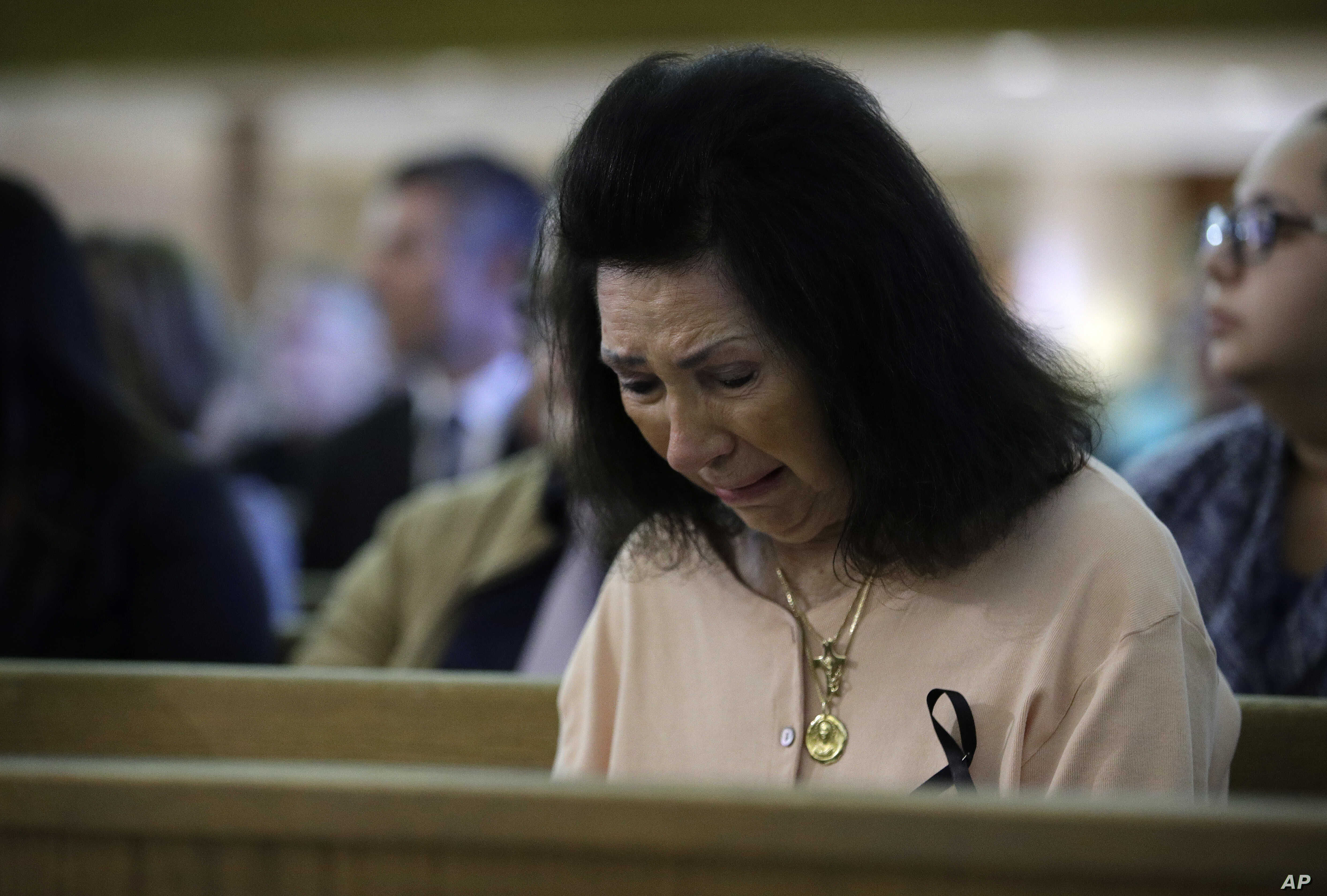 A woman reacts during a special service at Guardian Angel Cathedral after the mass shooting on the Las Vegas Strip, Oct. 2, 2017, in Las Vegas.