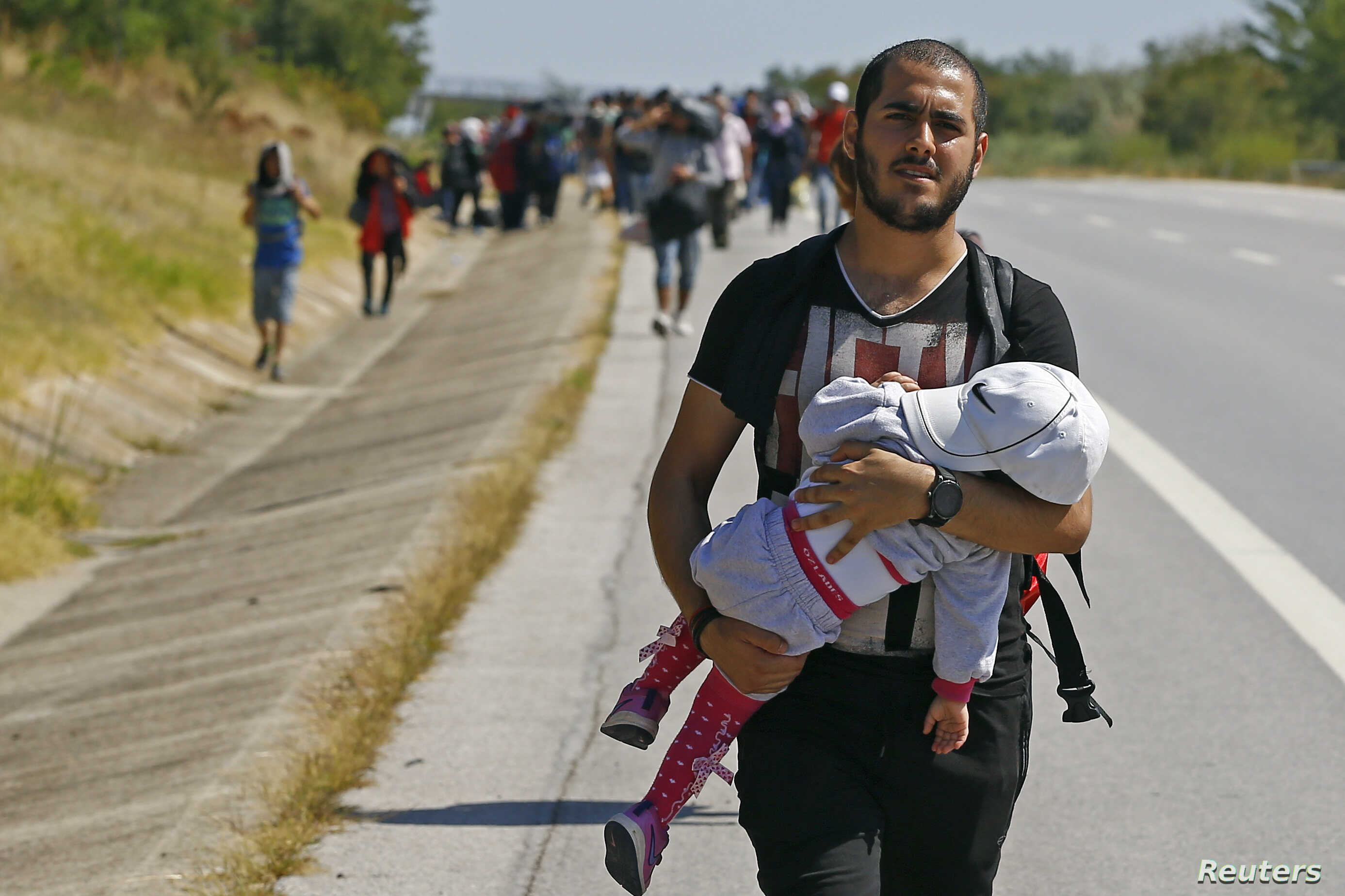 A Syrian migrant carries a baby as he walks towards the Greece border on a road near Edirne, Turkey, Sept. 15, 2015.